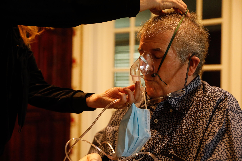 Nanette Kearl puts an oxygen mask on her husband, Thomas Kearl, at their house in Salt Lake City on Thursday