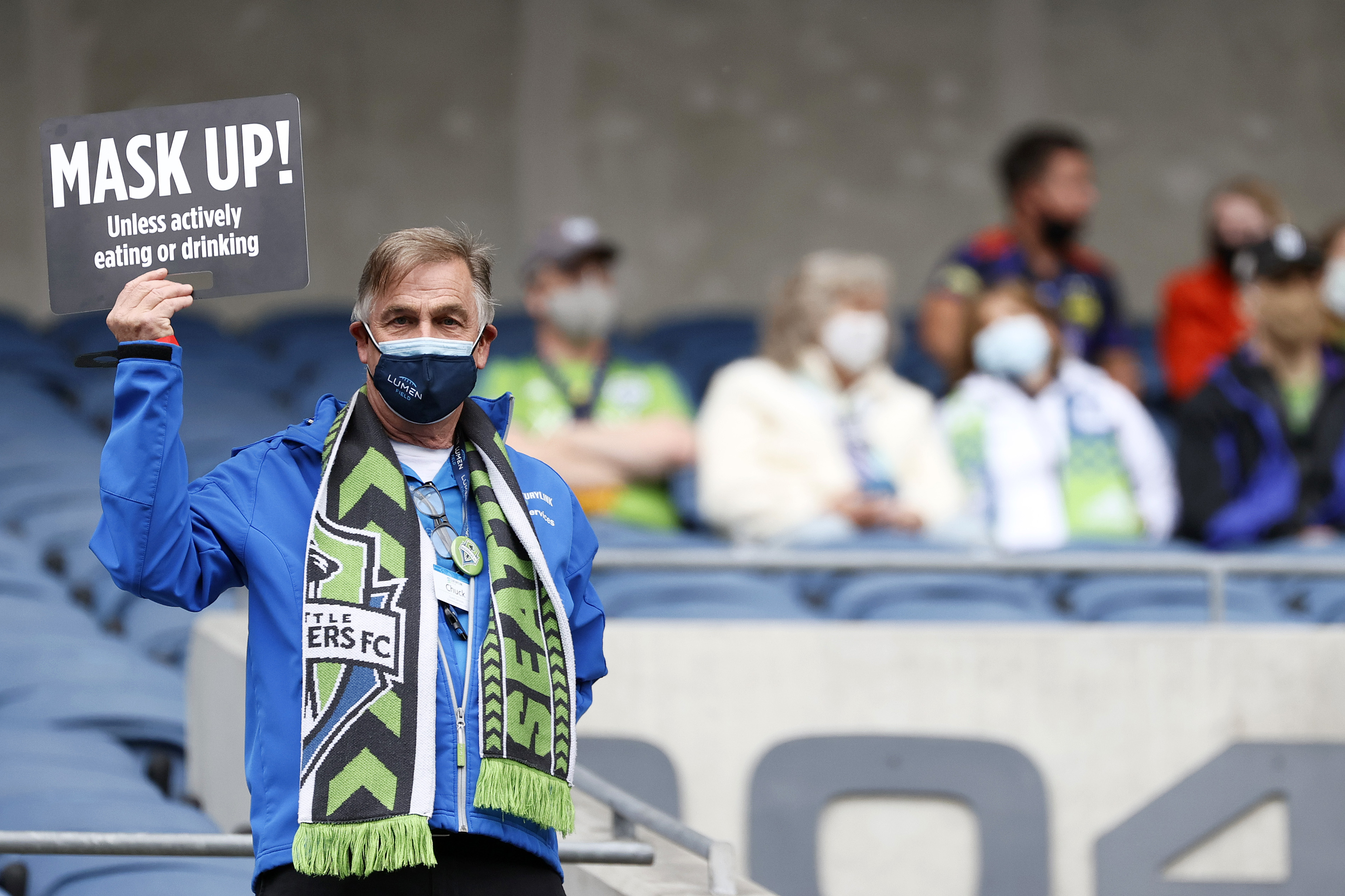 """A man wearing a mask and a Seattle Sounders scarf holds up a sign that says """"Mask up! Unless actively eating or drinking,"""" with several fans in the stands in the background, also wearing masks."""