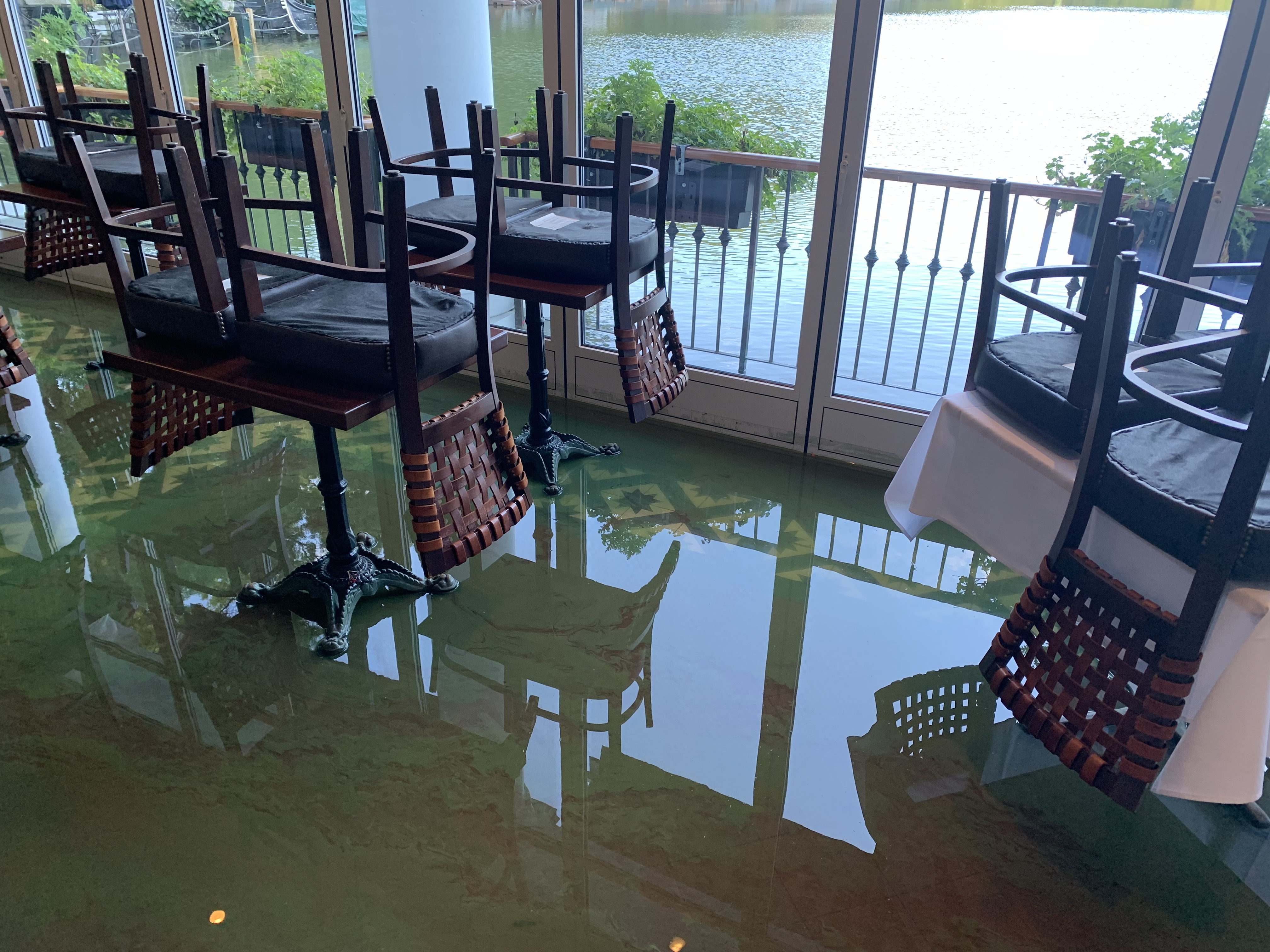 Water covers the floor of an open dining room with tables and chairs next to a lake