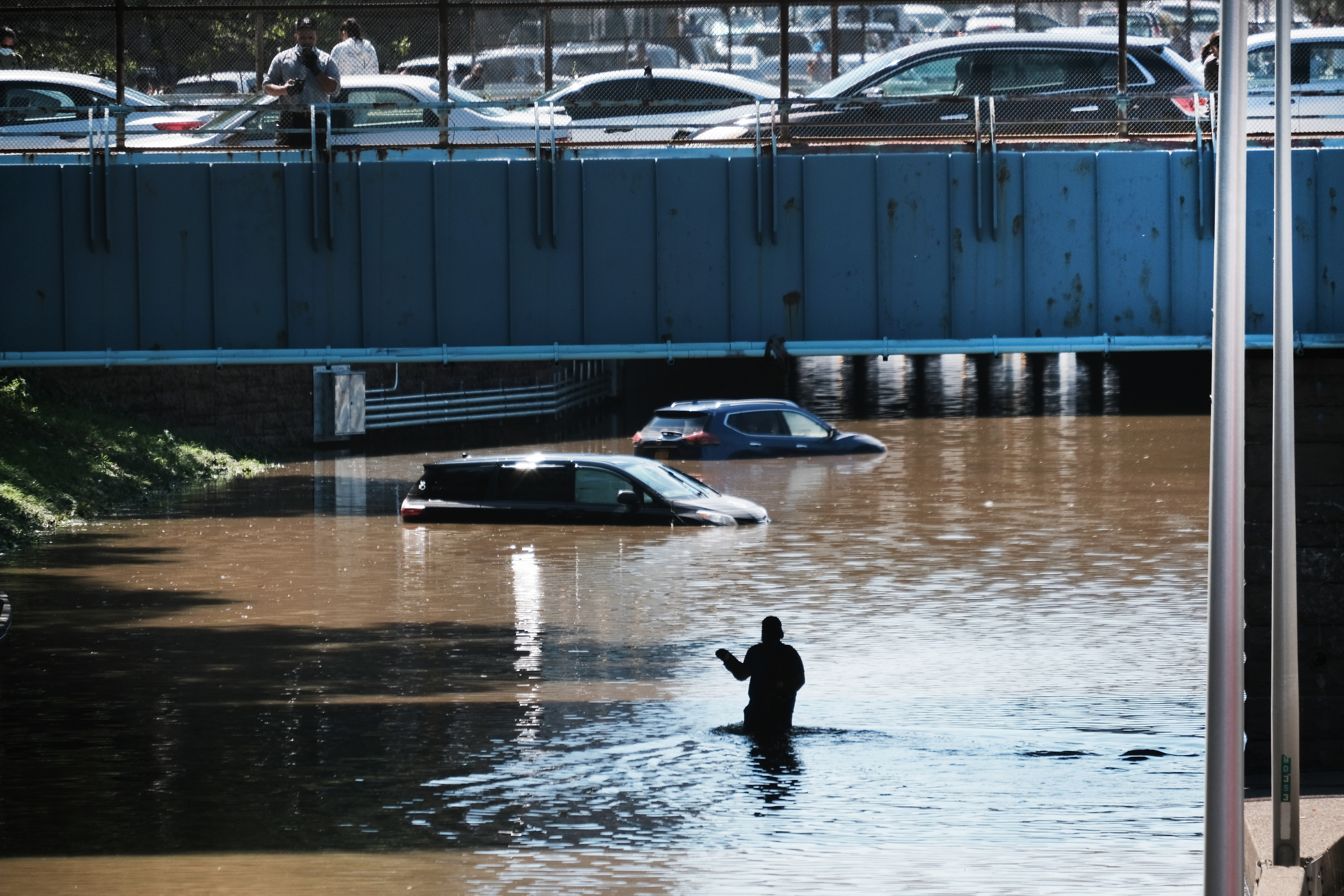 A person wades through a flooded freeway as cars sit abandoned halfway under water.