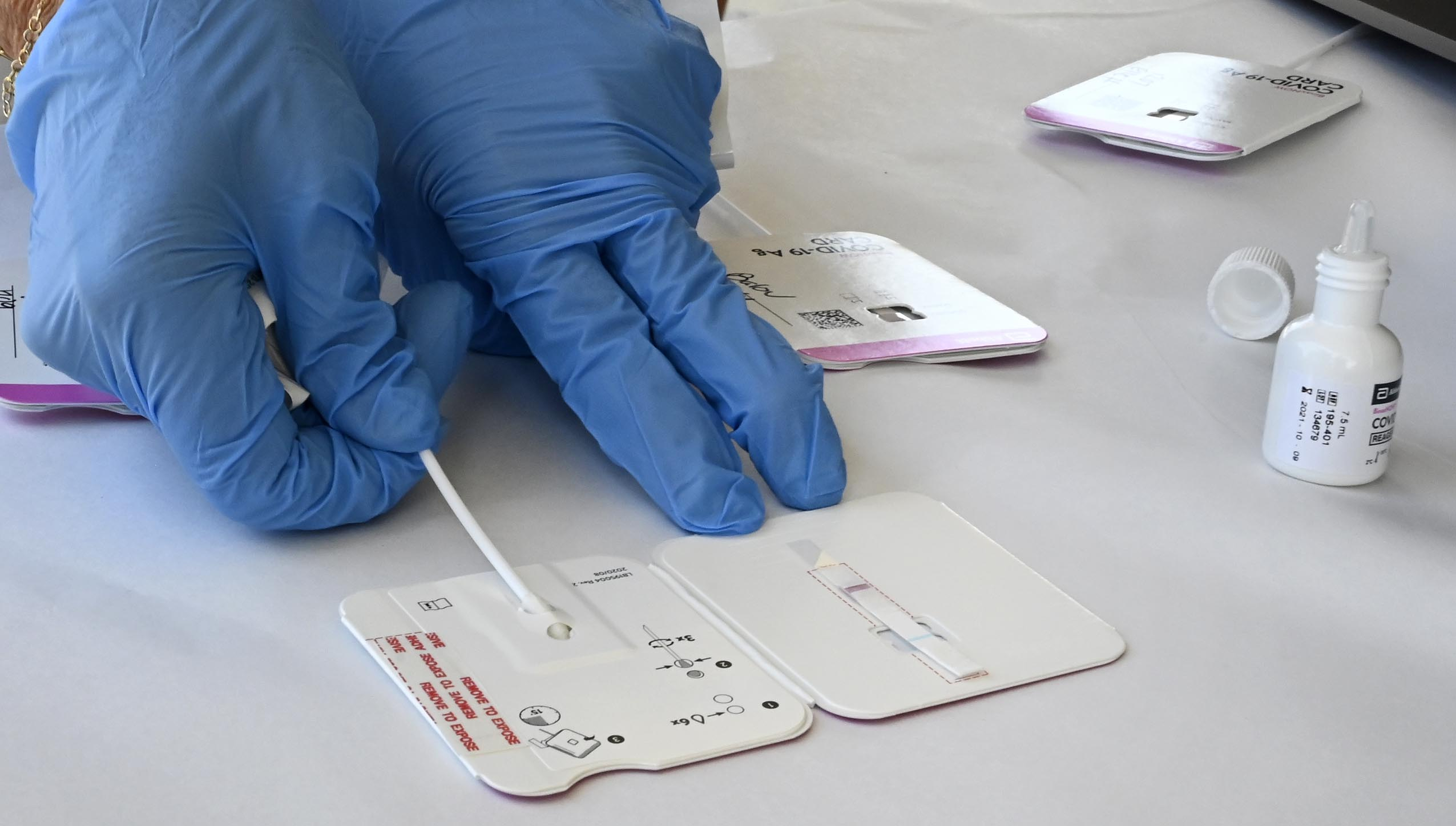 A close up of a health care worker's hands in blue gloves working with COVID testing swabs.