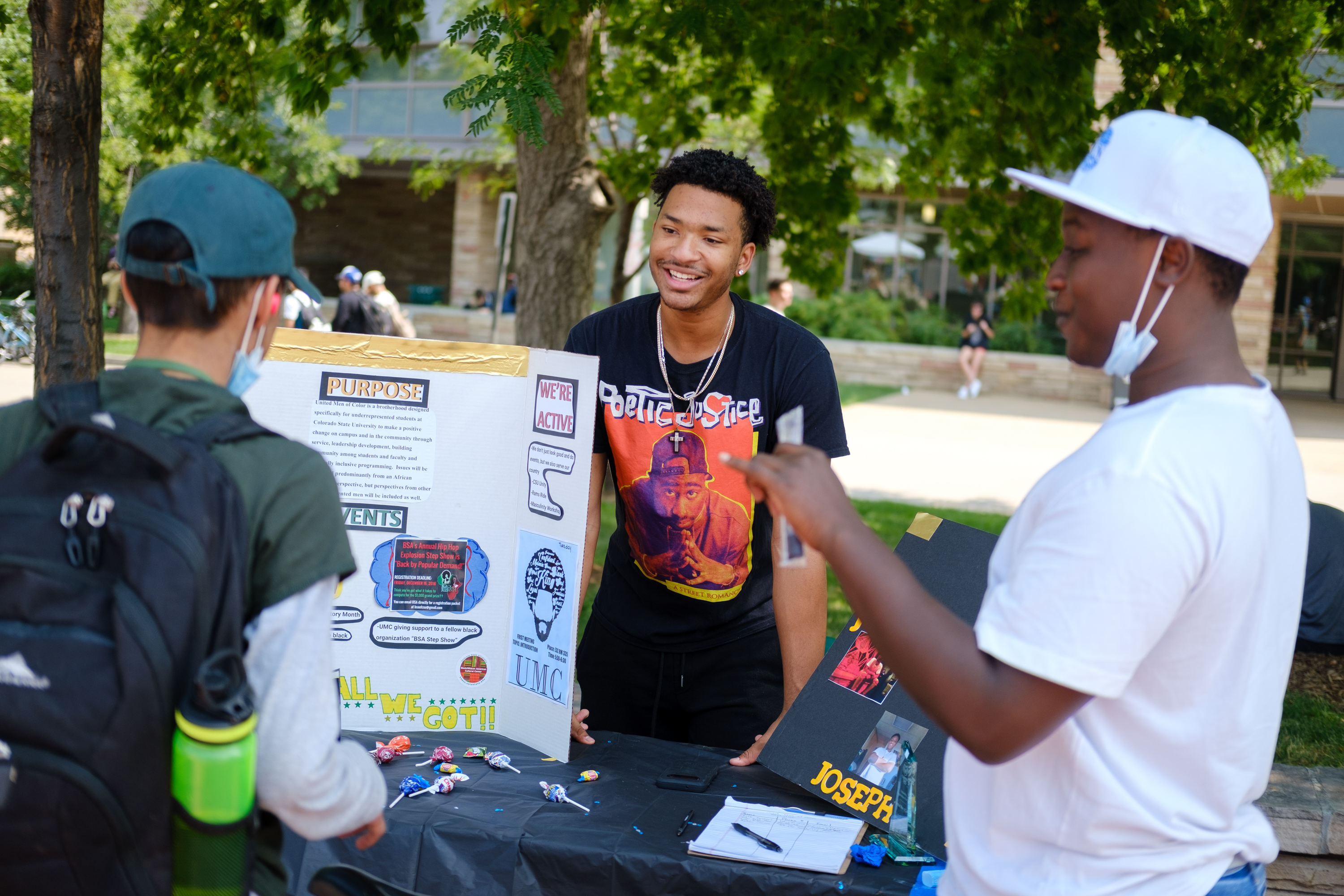Two young men talk to a fellow student student about their on-campus group, United Men of Color, during a student involvement fair.