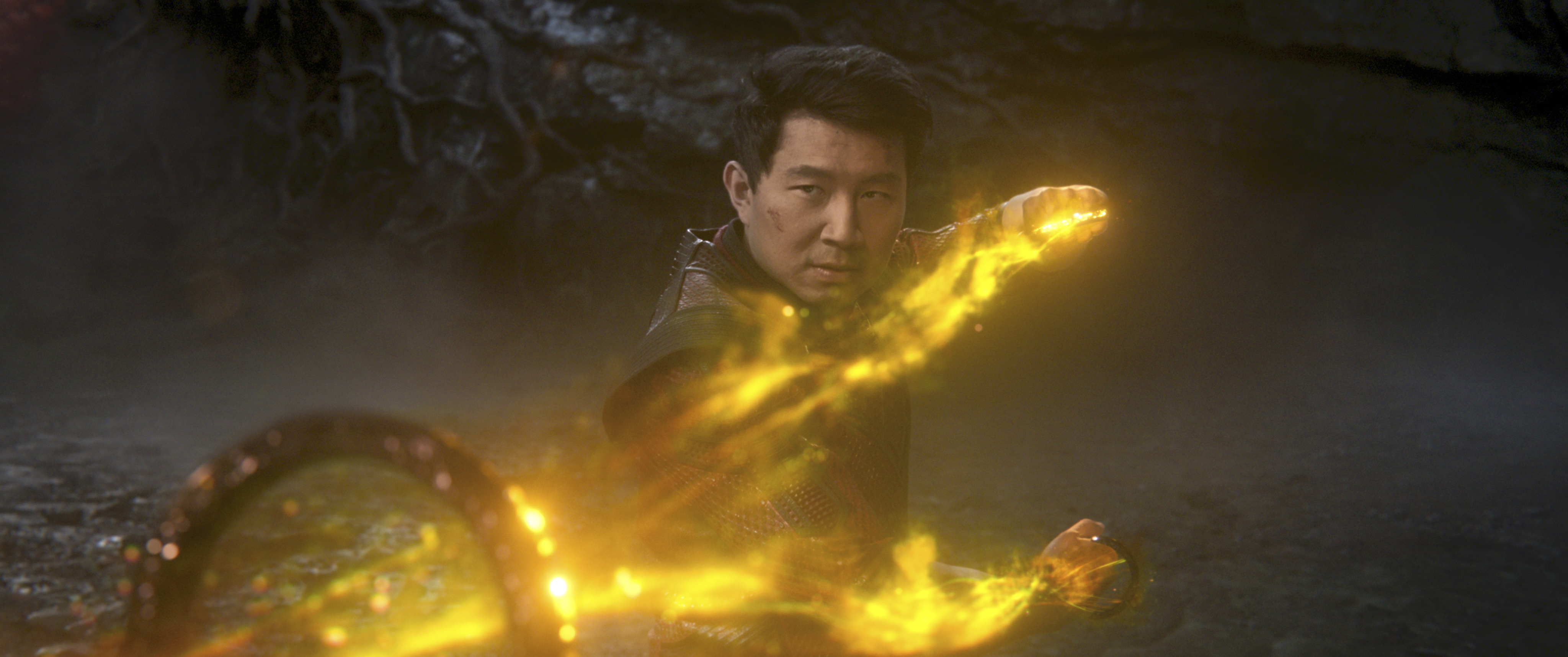 Simu Liu wields the Ten Rings, surrounded by yellow fire, as Shang-Chi in Shang-Chi and the Legend of the Ten Rings.