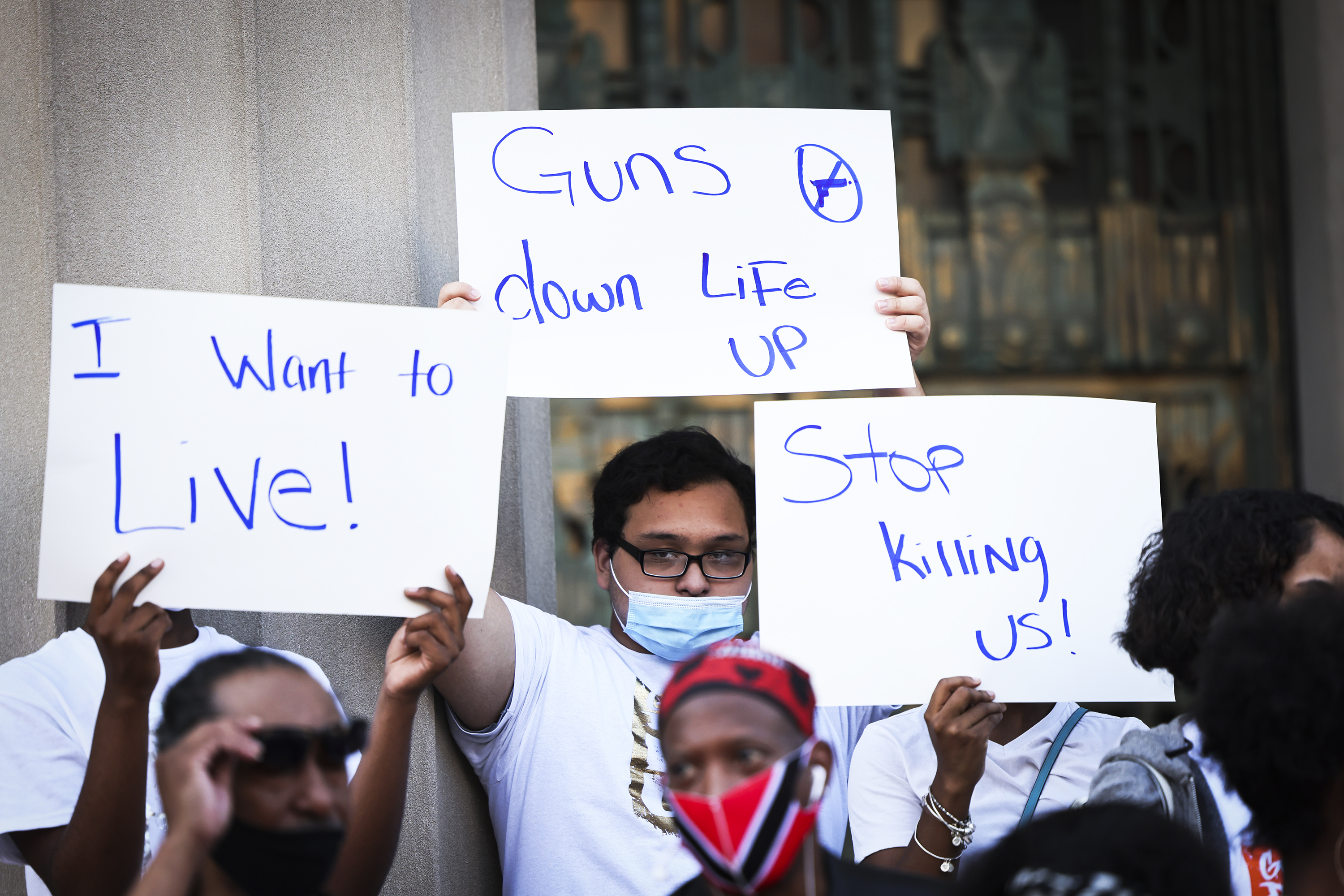 """People hold up signs such as """"Stop killing us!"""" at a rally."""
