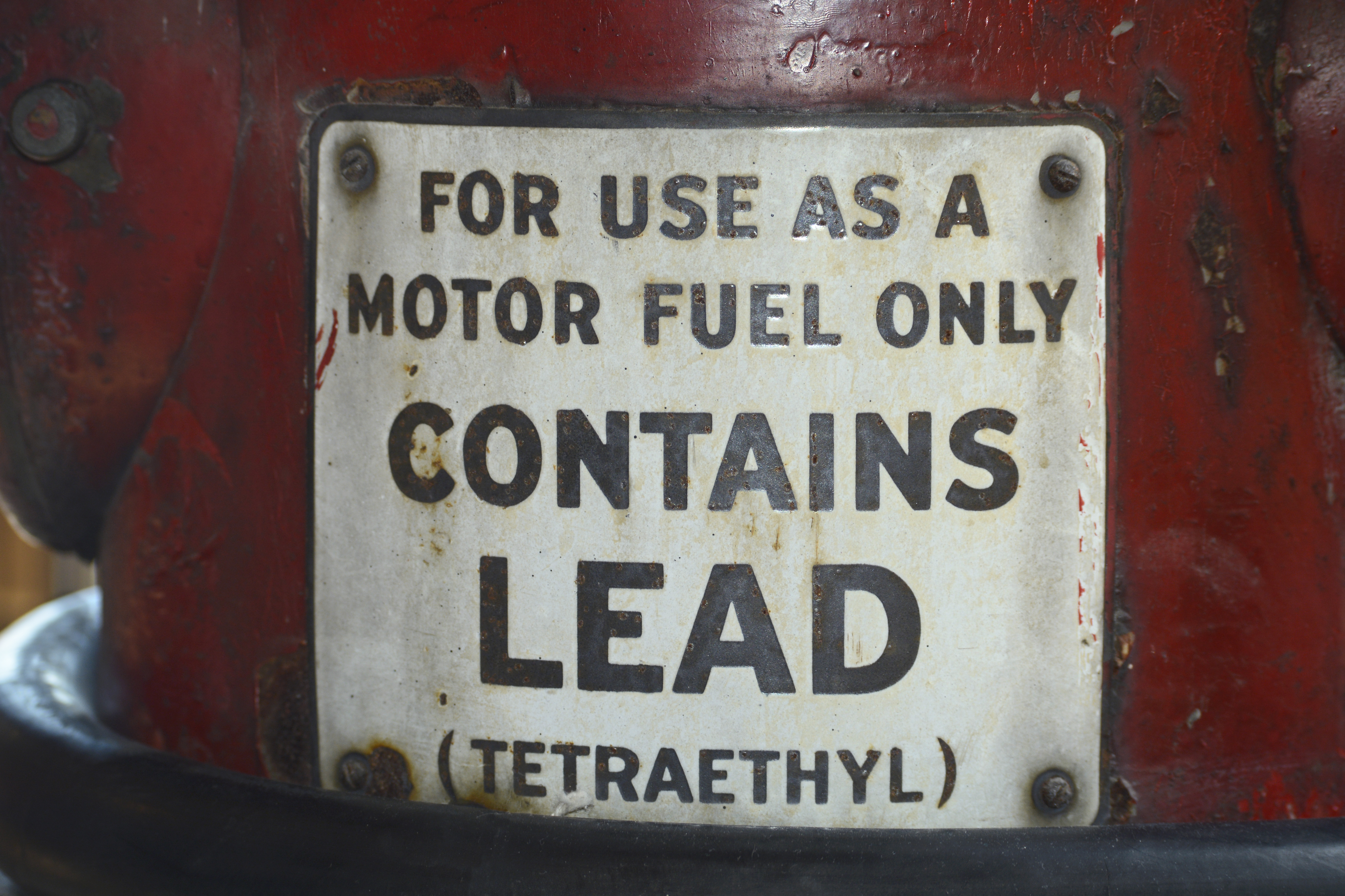 A sign on a vintage gasoline pump advises that the gas contains lead (tetraethyl).