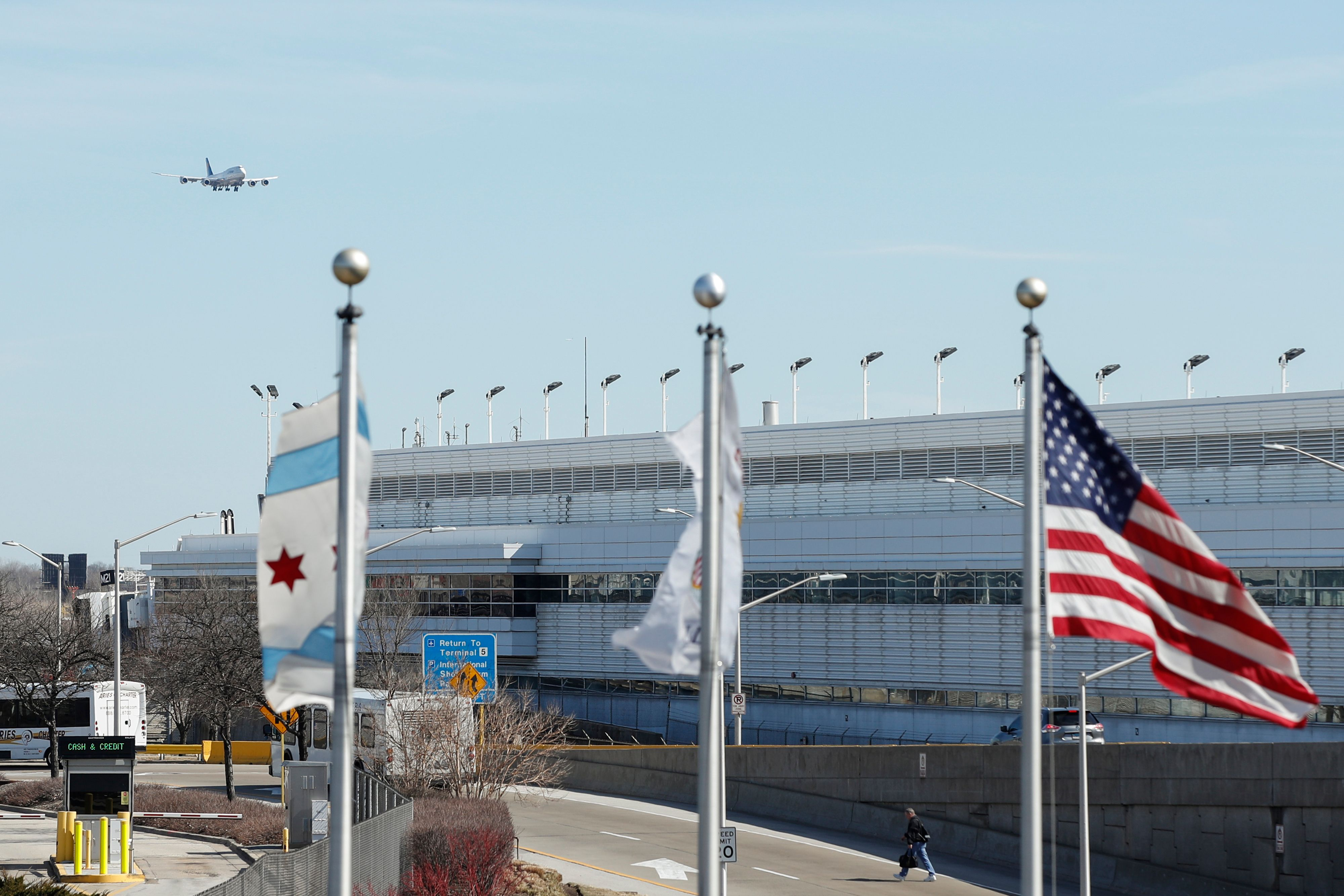 A view of Chicago O'Hare airport as a jet is flying in. The flags of Chicago, Illinois, and the United States fly in the foreground.