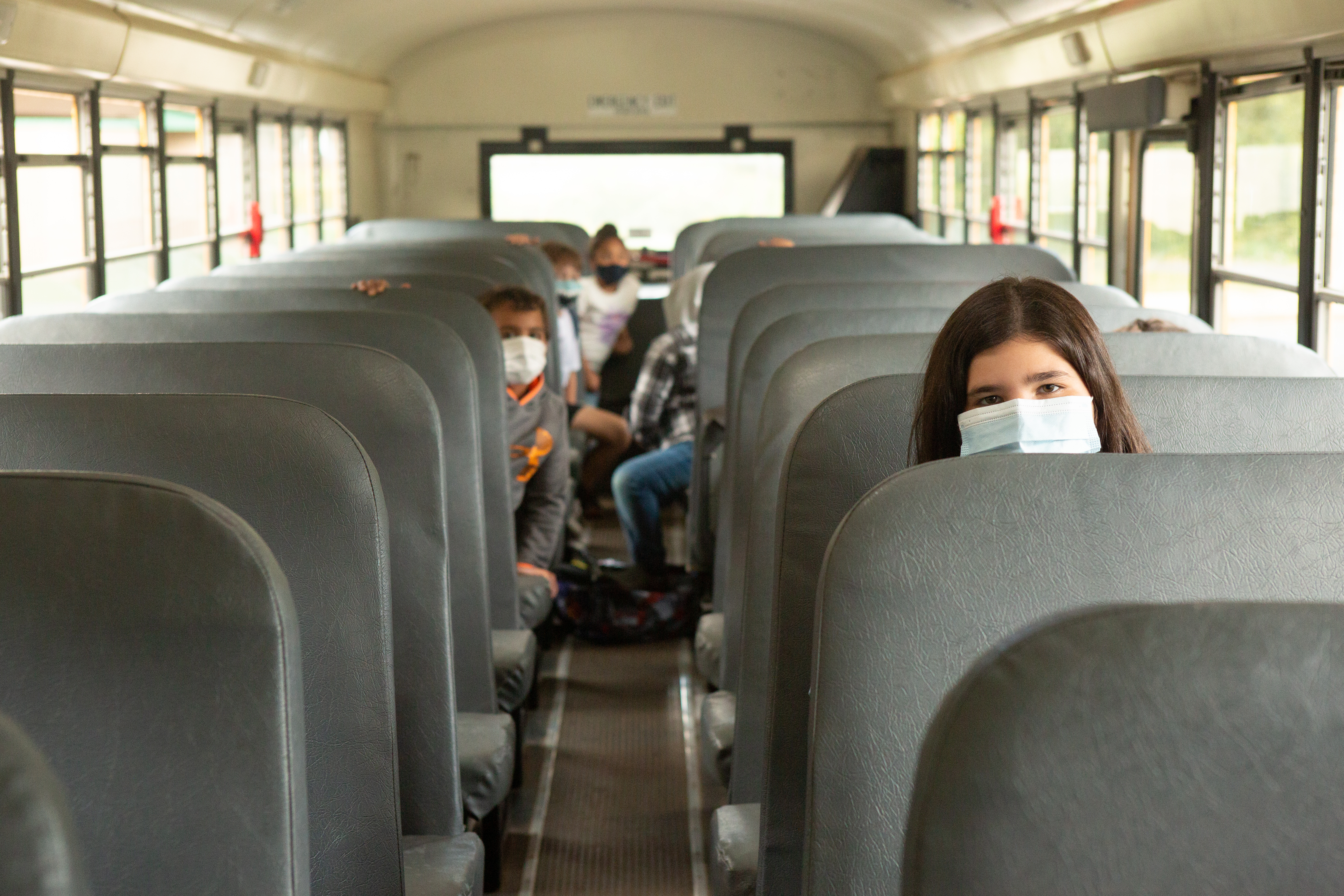 Several students, wearing blue face masks, sit on a bus with gray seats waiting as students wait to depart from school.