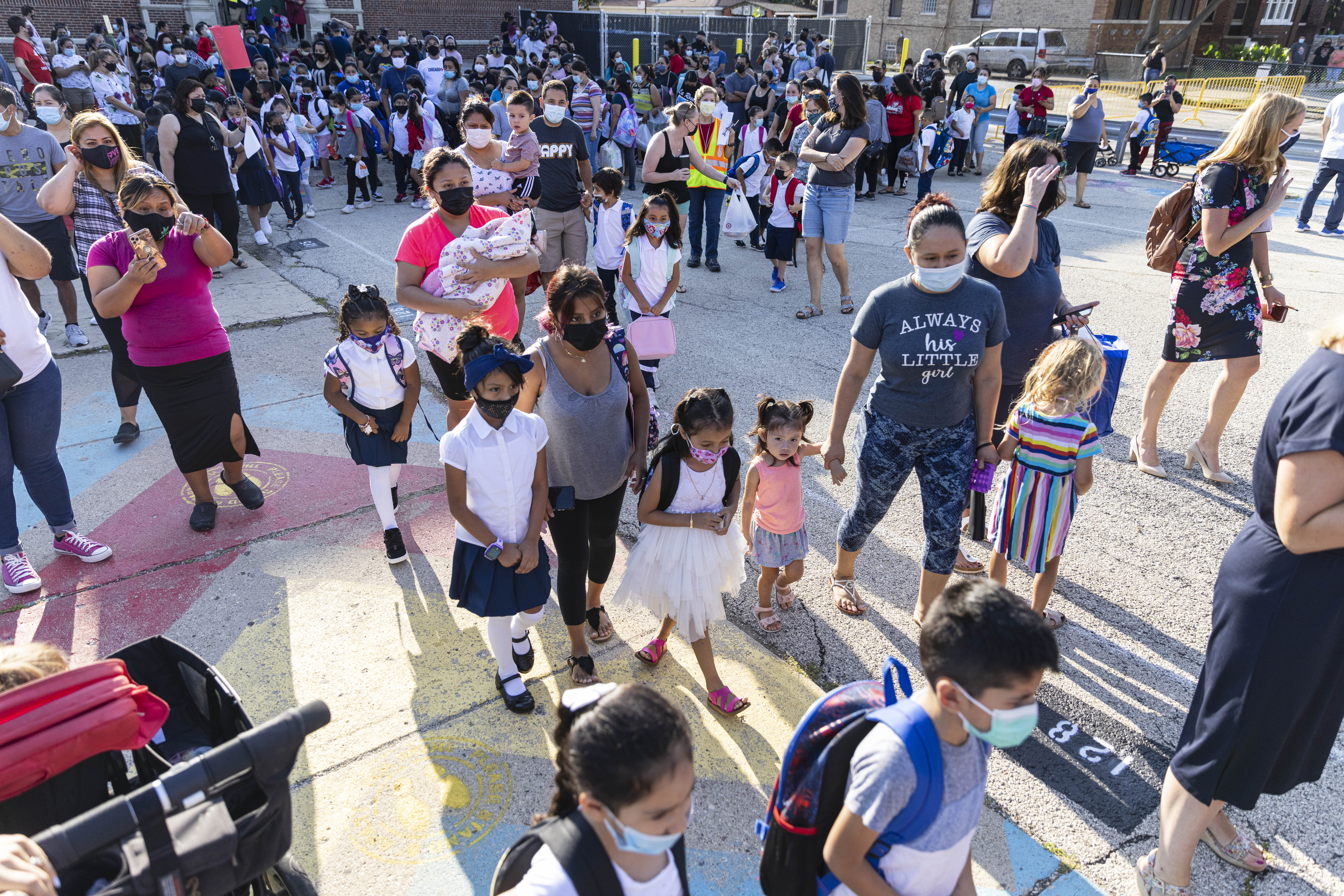 Students and parents wait in line as students return to school on the first day of classes at Alessandro Volta Elementary School 4950 N Avers Ave. in Albany Park, Monday, Aug. 30, 2021.