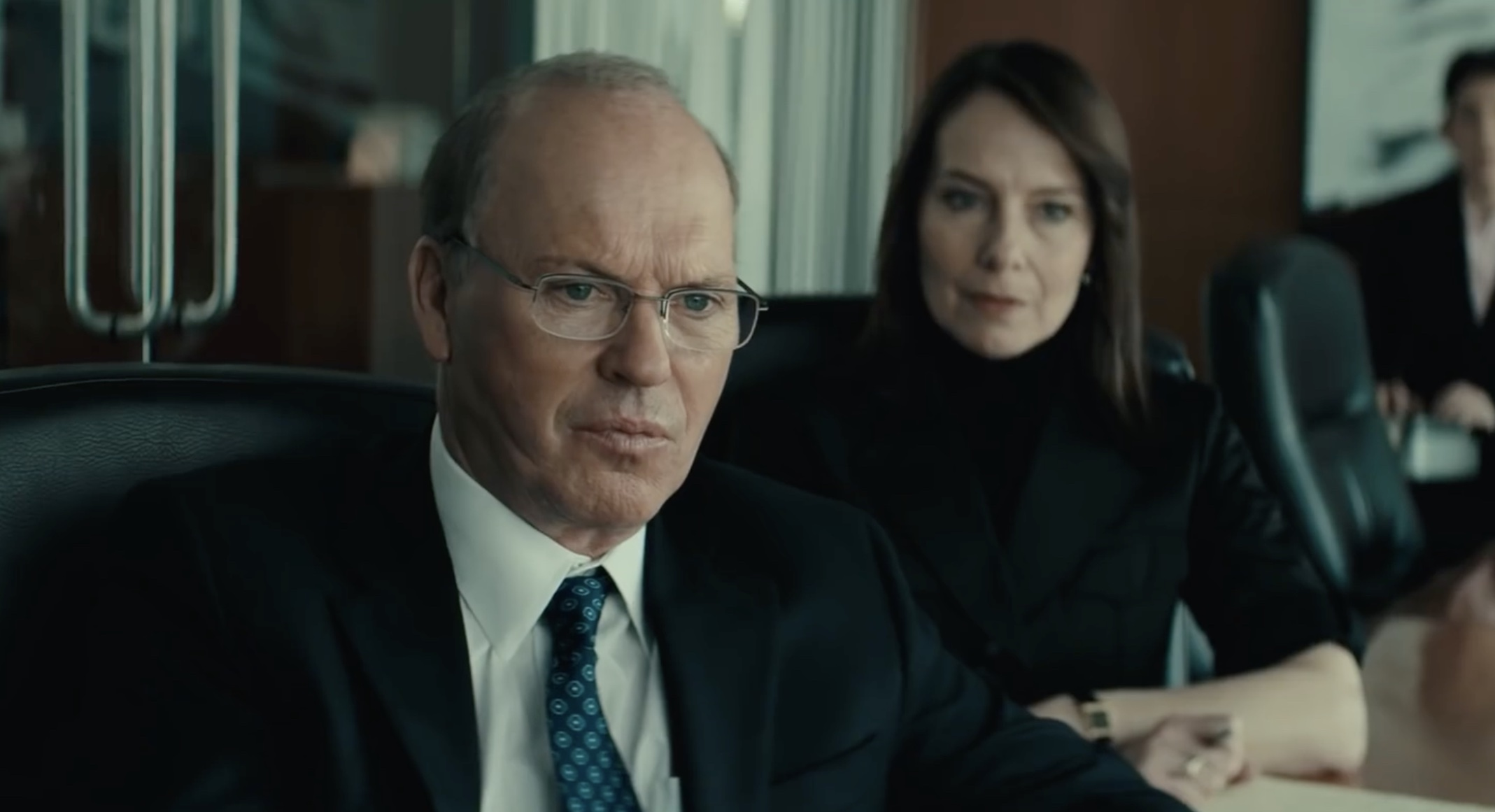 Michael Keaton and Amy Ryan in a conference room grimacing in Worth