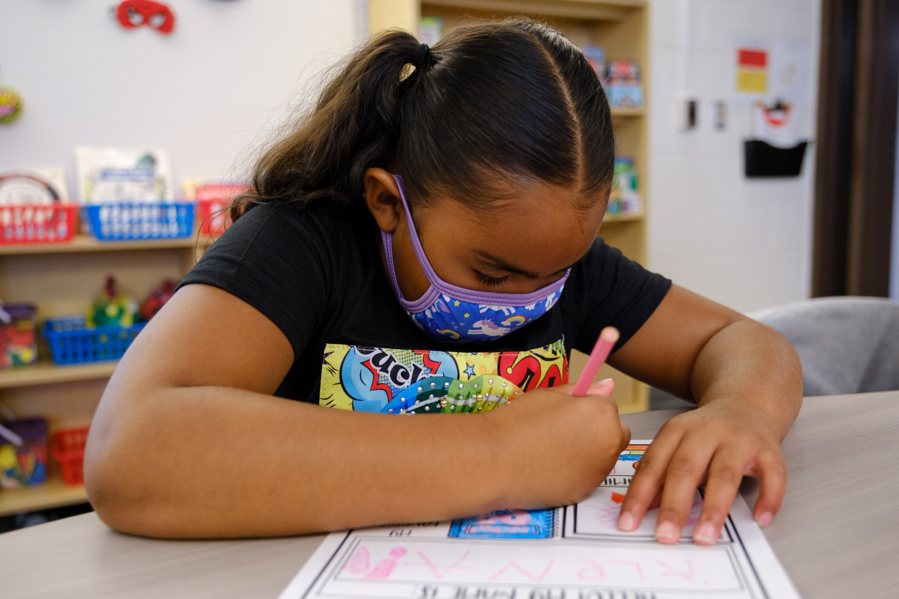 A young girl wearing a mask writes on a worksheet at her desk.