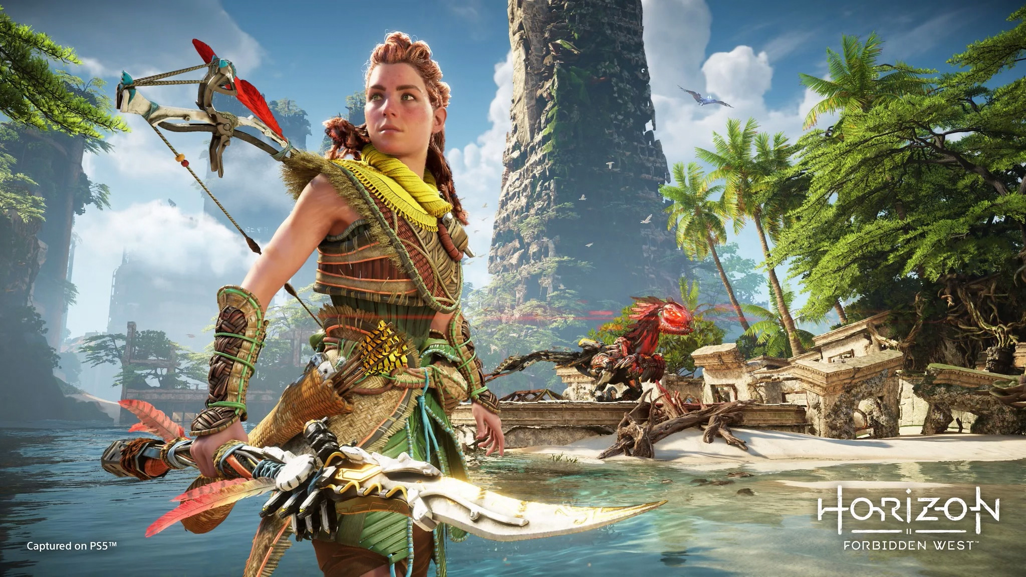 Aloy standing on a beach holding a spear looking into the distance while a Machine prowls in the background in Horizon Forbidden West