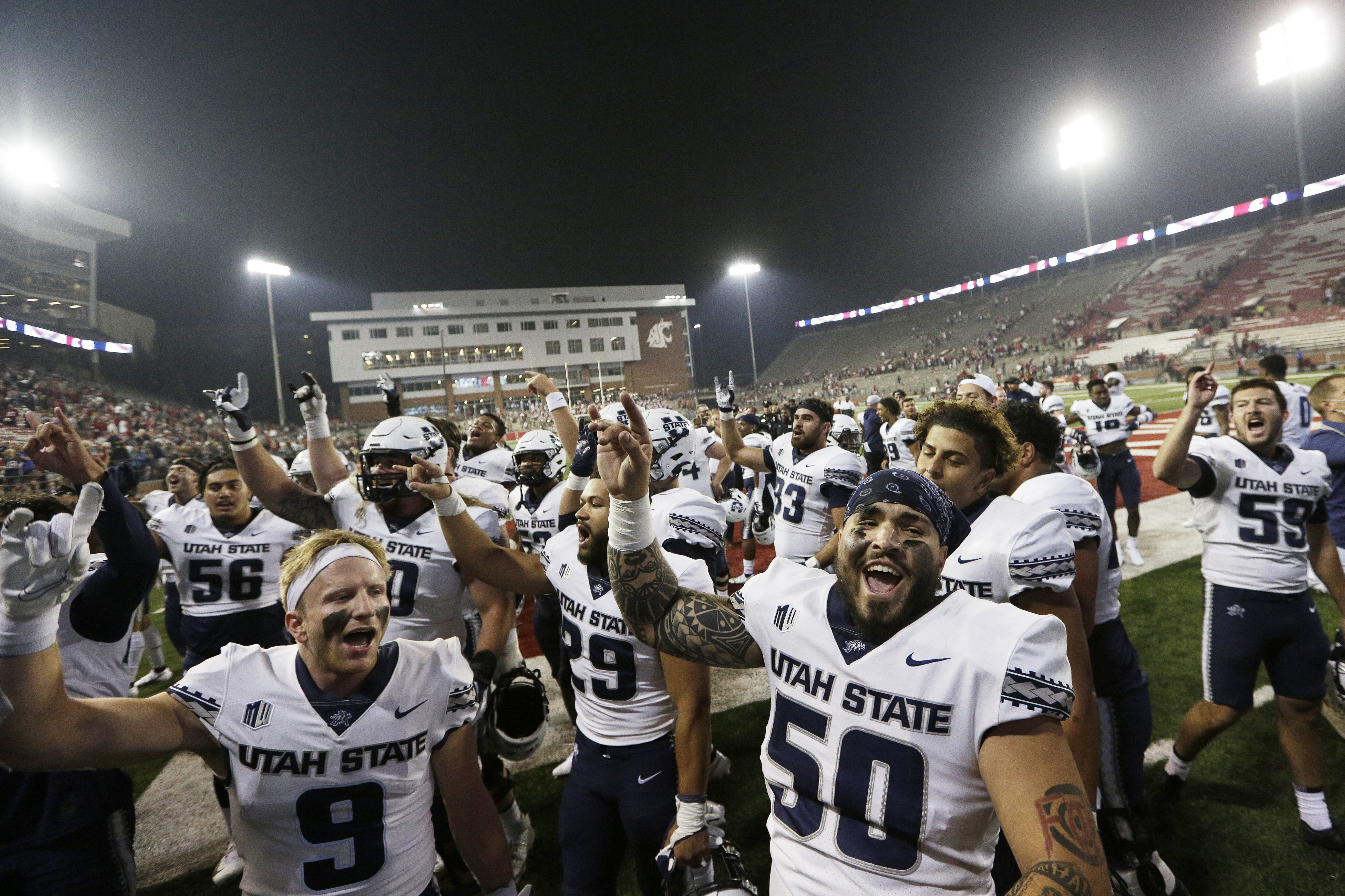 Utah State players sing the school's song while celebrating with fans after winning 26-23 against Washington State.