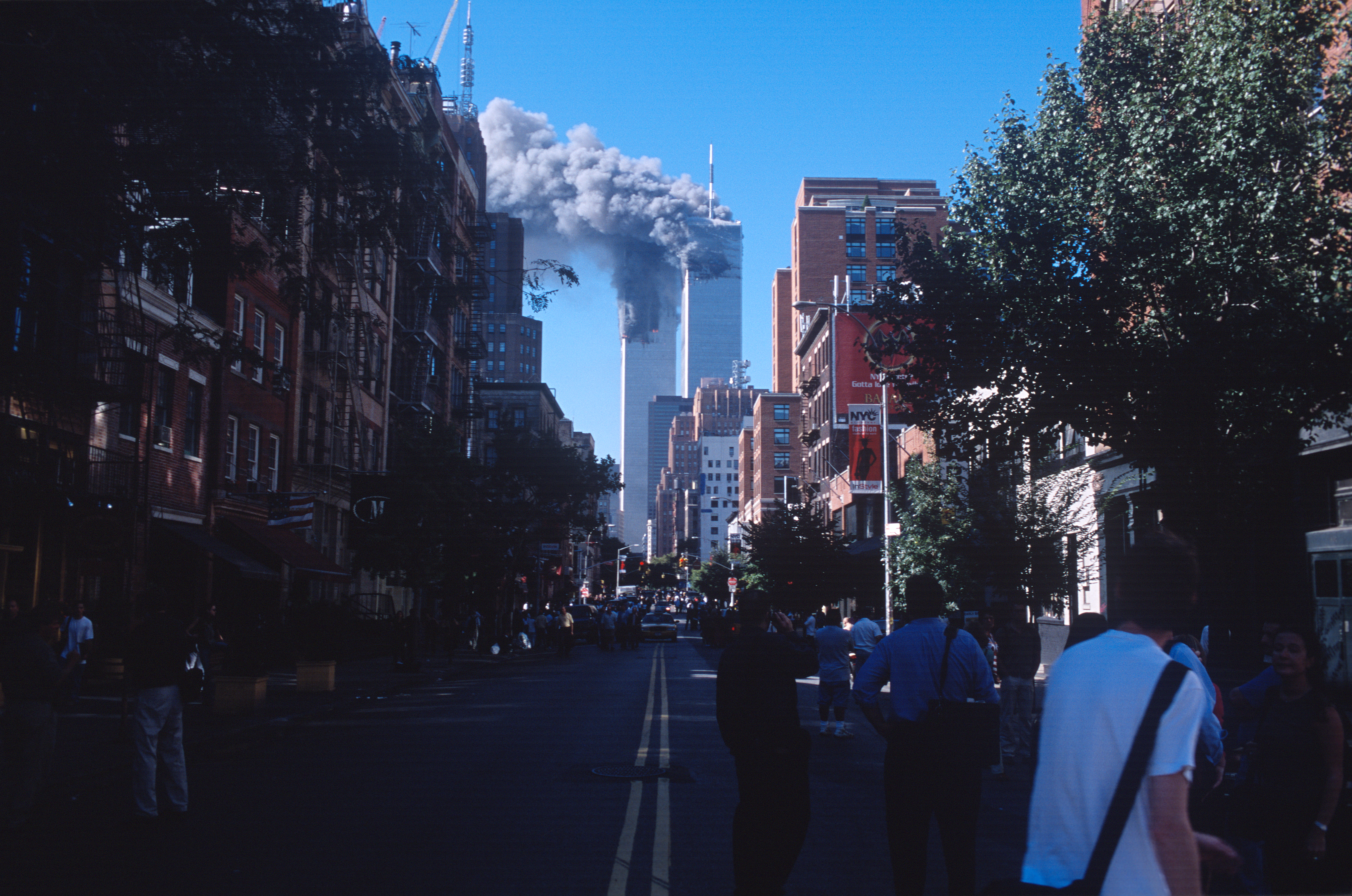 People look on as smoke from the burning World Trade Center towers fills up the downtown Manhattan skyline after both buildings were attacked by airplanes on September 11, 2001 in New York City.