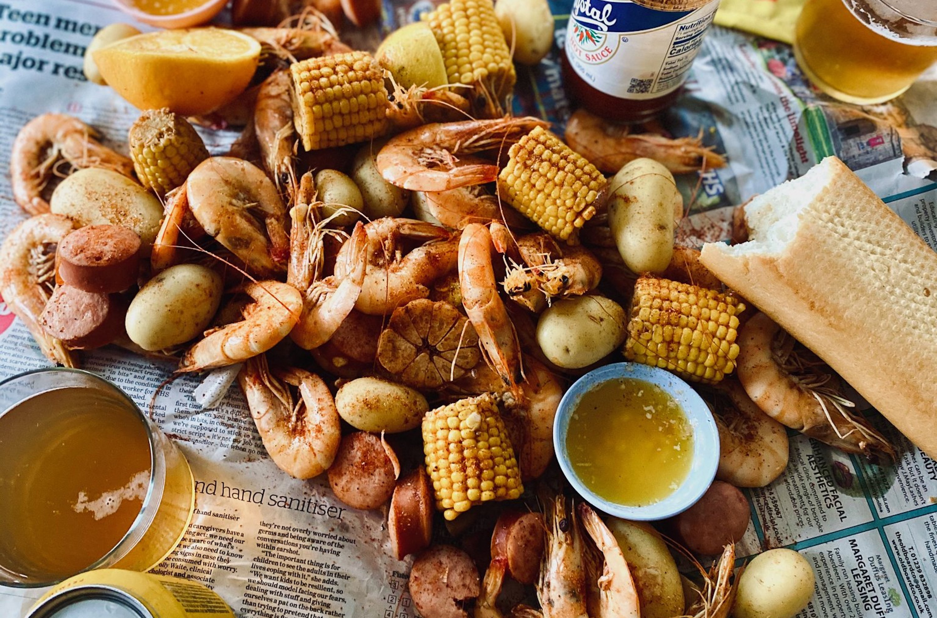 Corn, shrimp, potatoes, andouille on newspaper in a shrimp boil, with Crystal hot sauce and beers