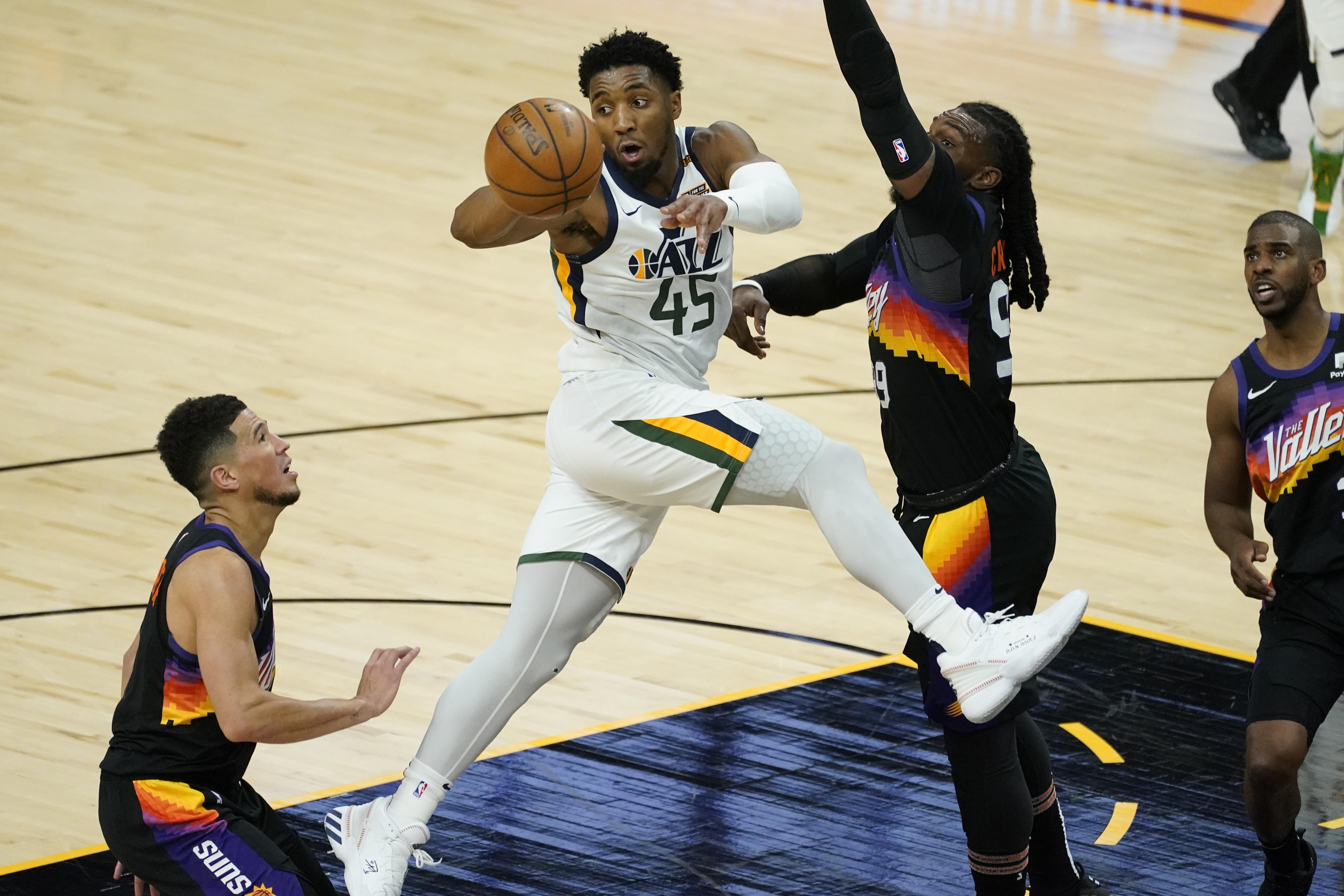 Utah Jazz guard Donovan Mitchell dishes off as Phoenix Suns forward Jae Crowder defends Wednesday, April 7, 2021, in Phoenix.