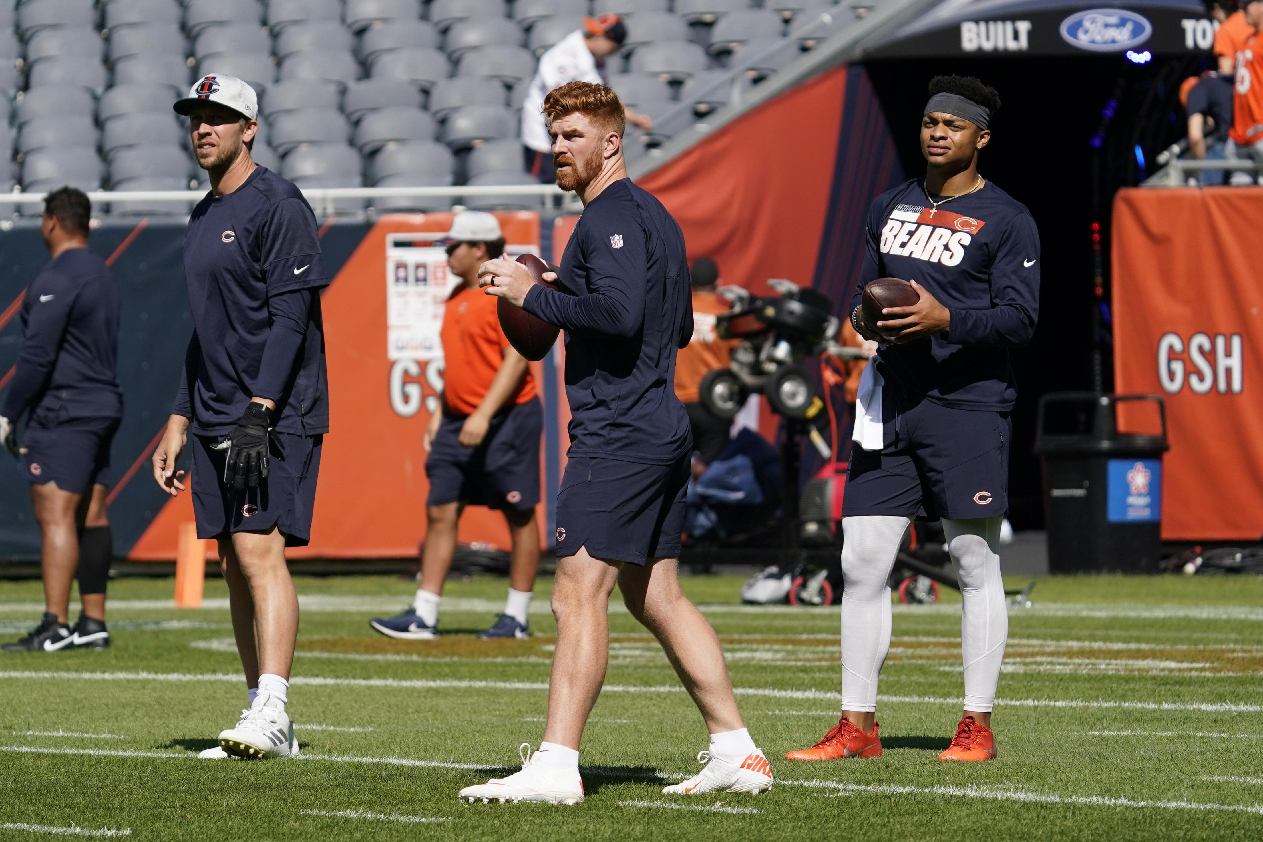 Bears quarterback Andy Dalton, center, looks to pass as fellow quarterbacks Nick Foles, left, and Justin Fields watch.