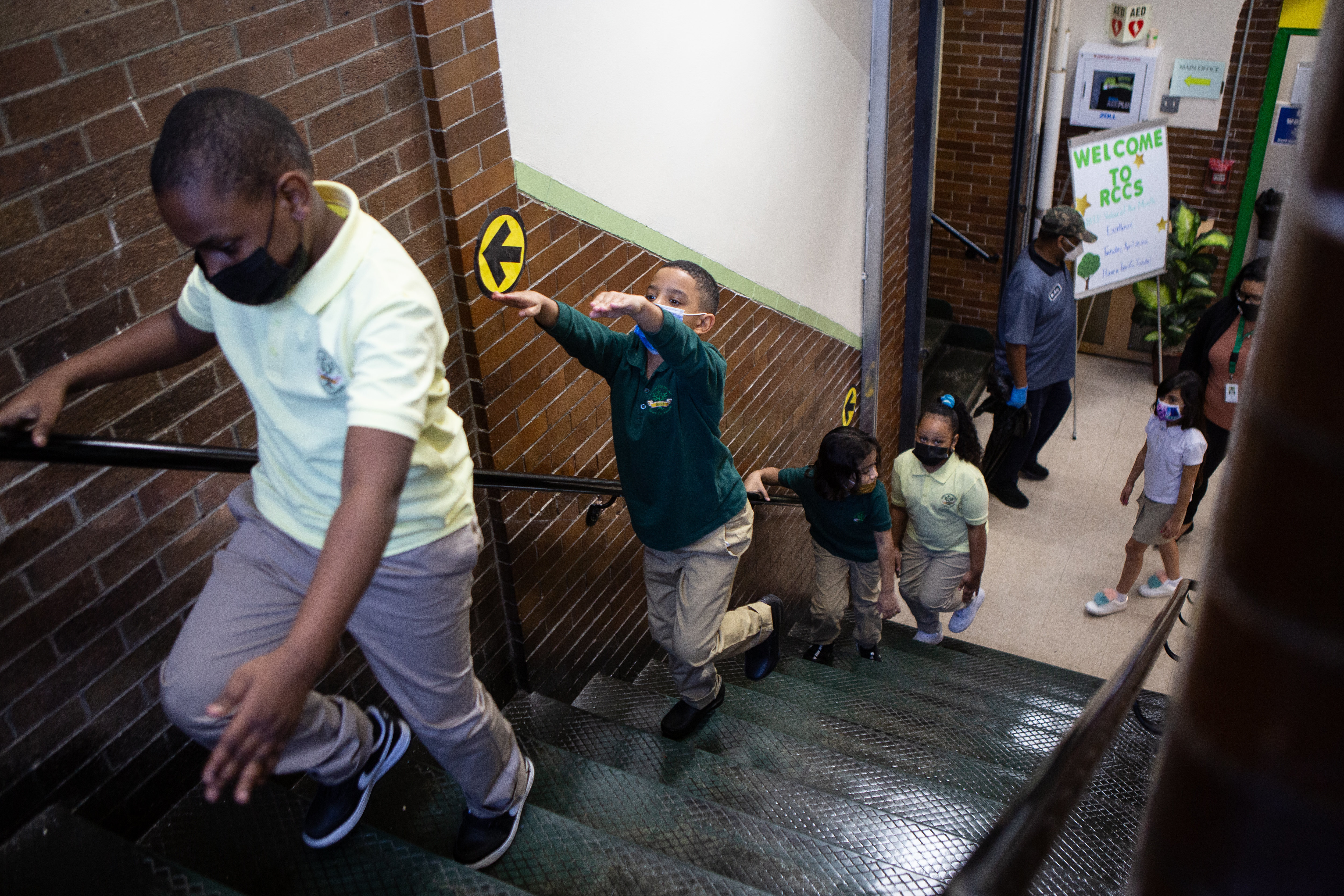 Masked second grade students walk up a stairwell, with one boy raising his arms in the air to practice arm's-length social distancing.