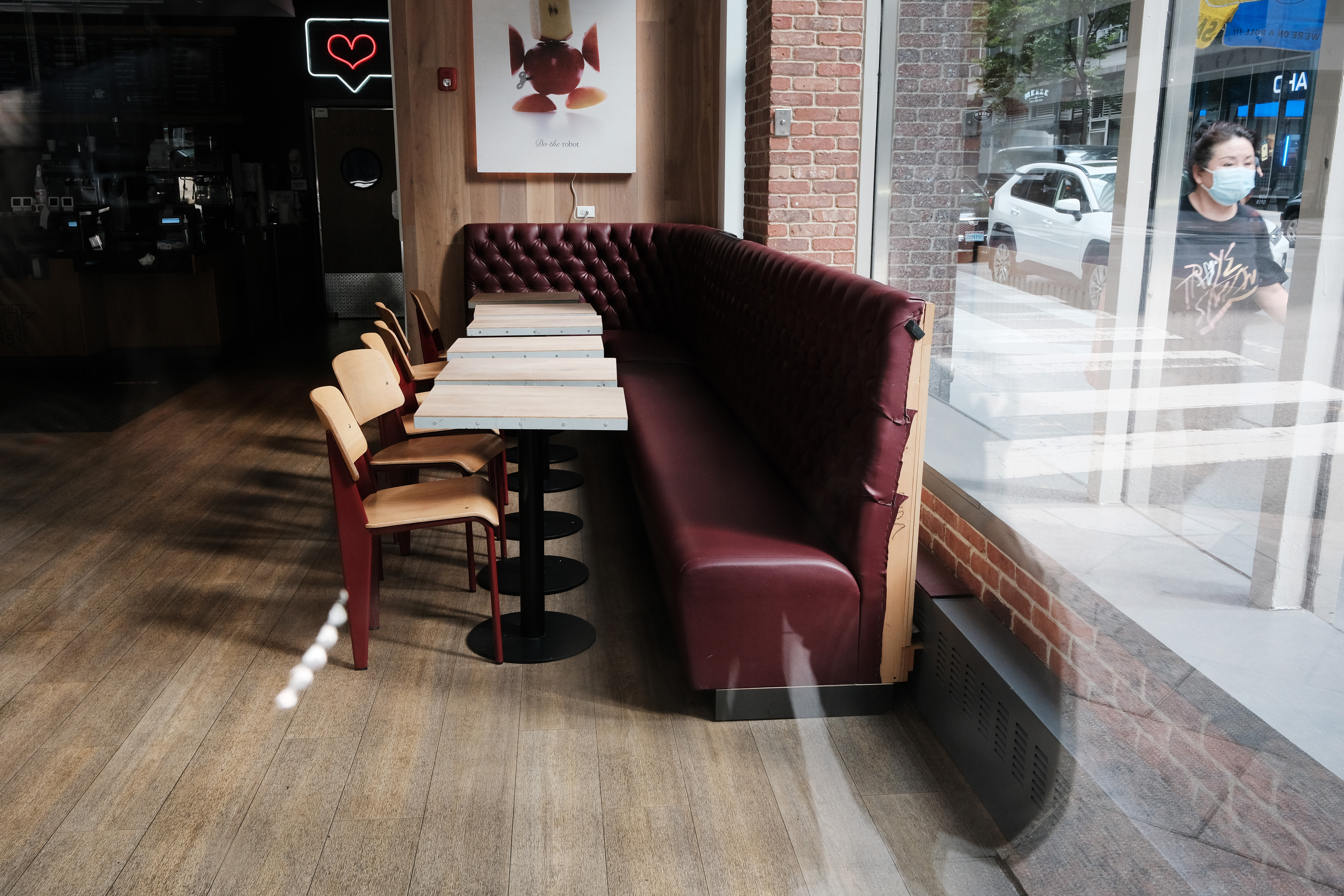 A restaurant with booths, white tables, and chairs next to storefront windows sits closed in midtown on August 30, 2021 in New York City.