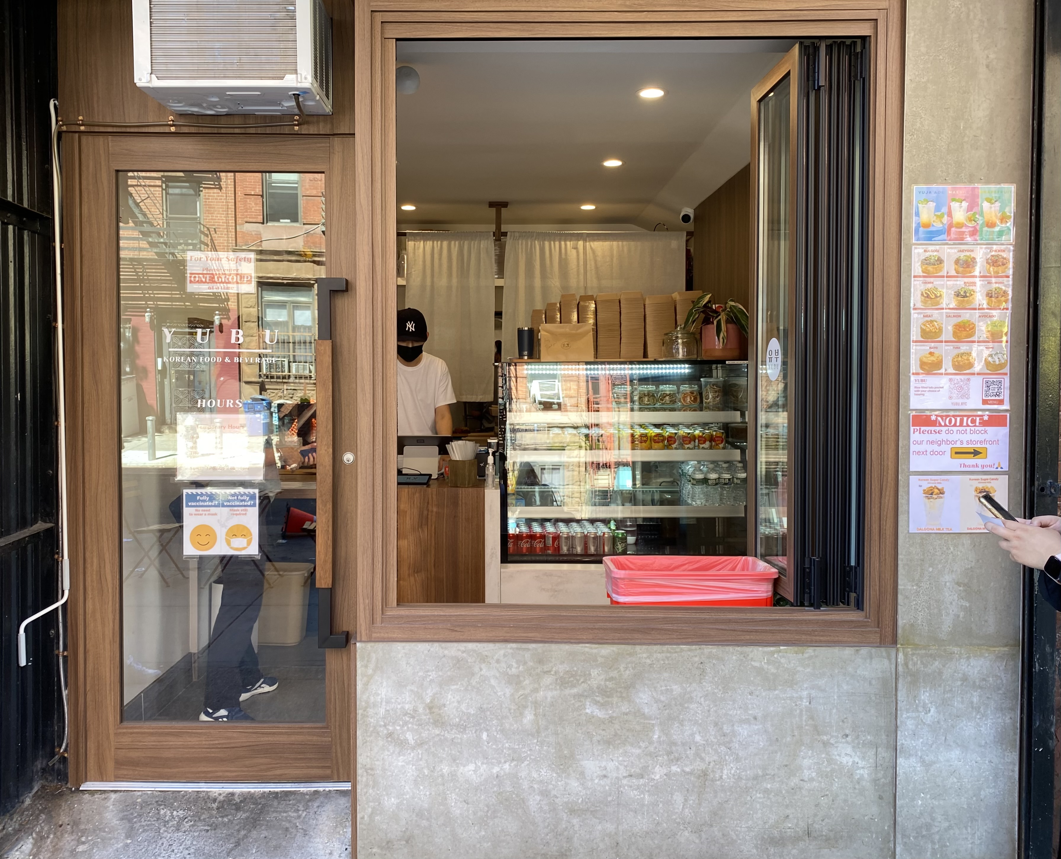 The inside of a small restaurant and a cashier is visible through an open window on a sunny day