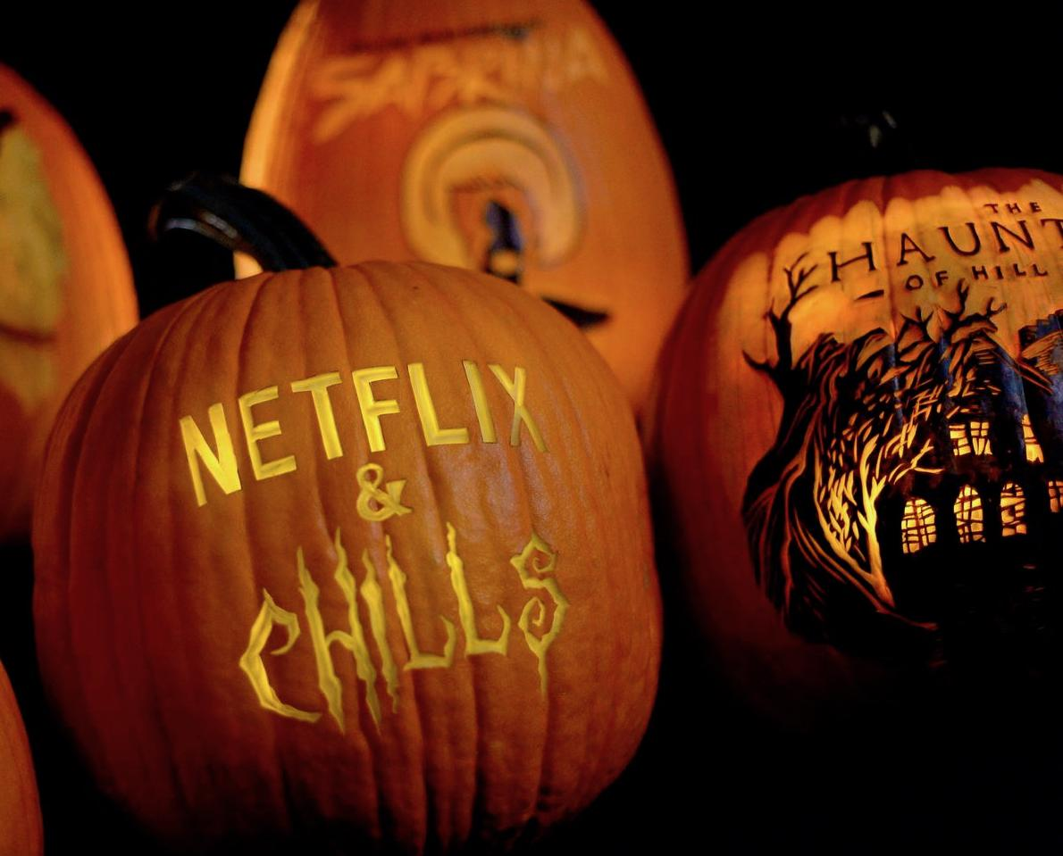 """a pumpkin with the words """"Netflix and Chills"""" carved on it"""