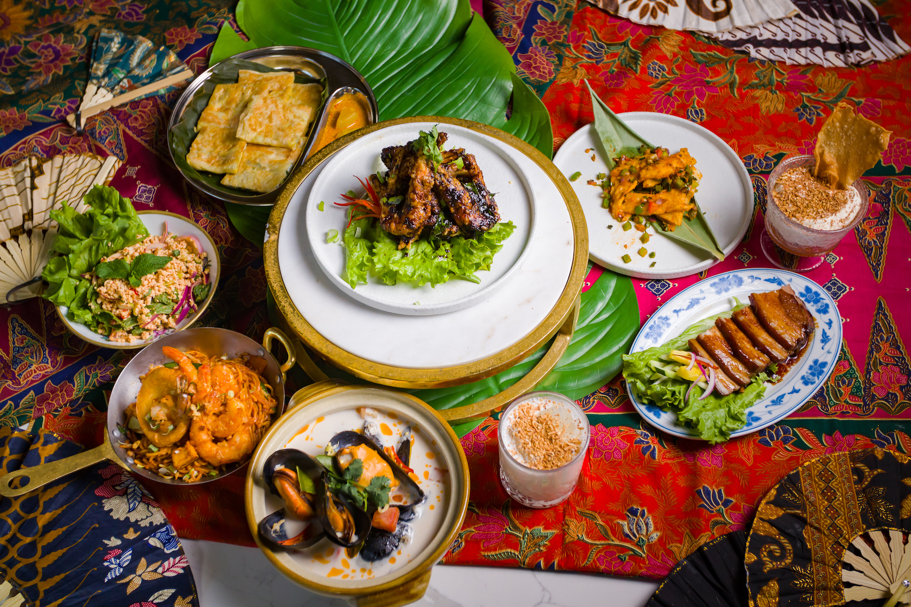 A spread of dishes on a colorful background at the Southeast Asian restaurant Wau