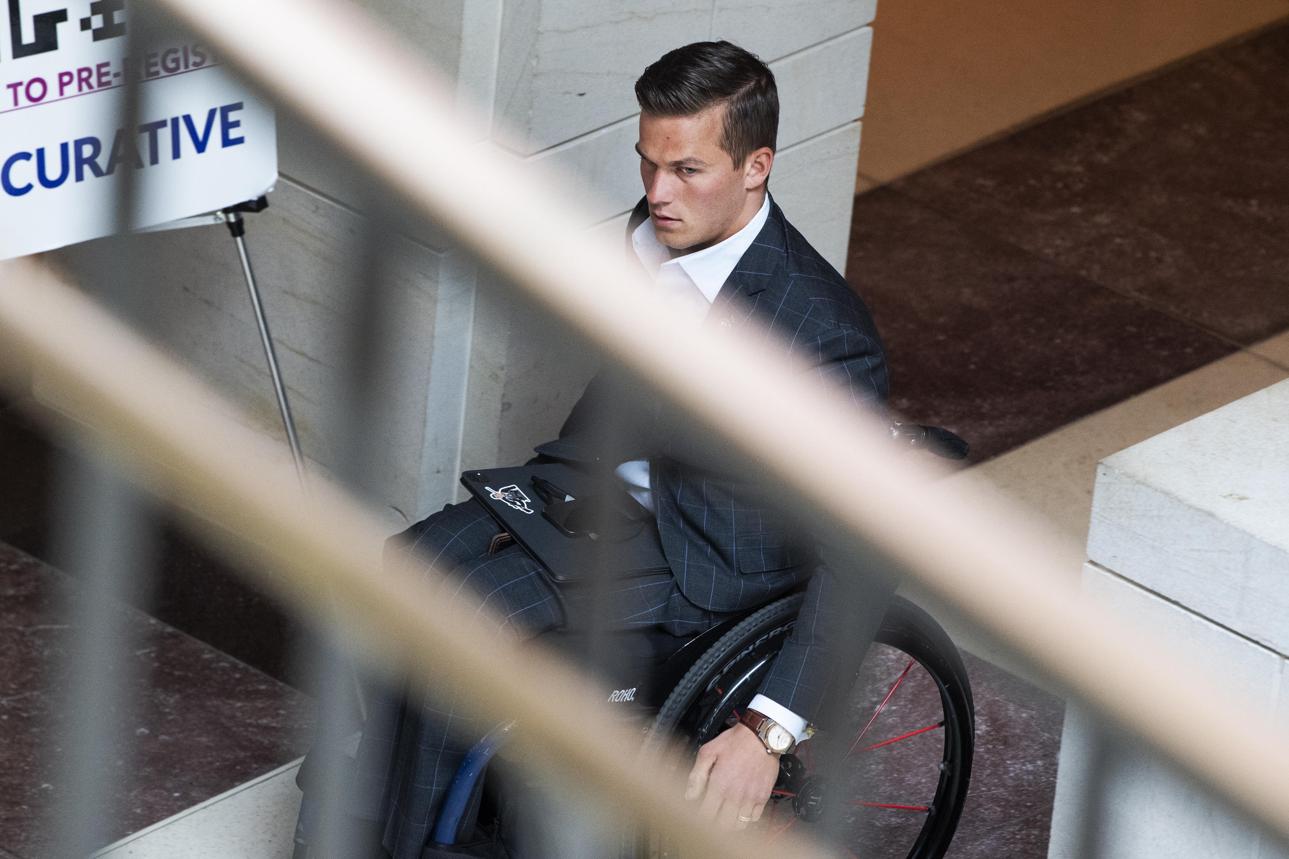 Madison Cawthorn, wearing a suit and moving his wheelchair down a hallway, viewed from above through the railing bars of a nearby staircase