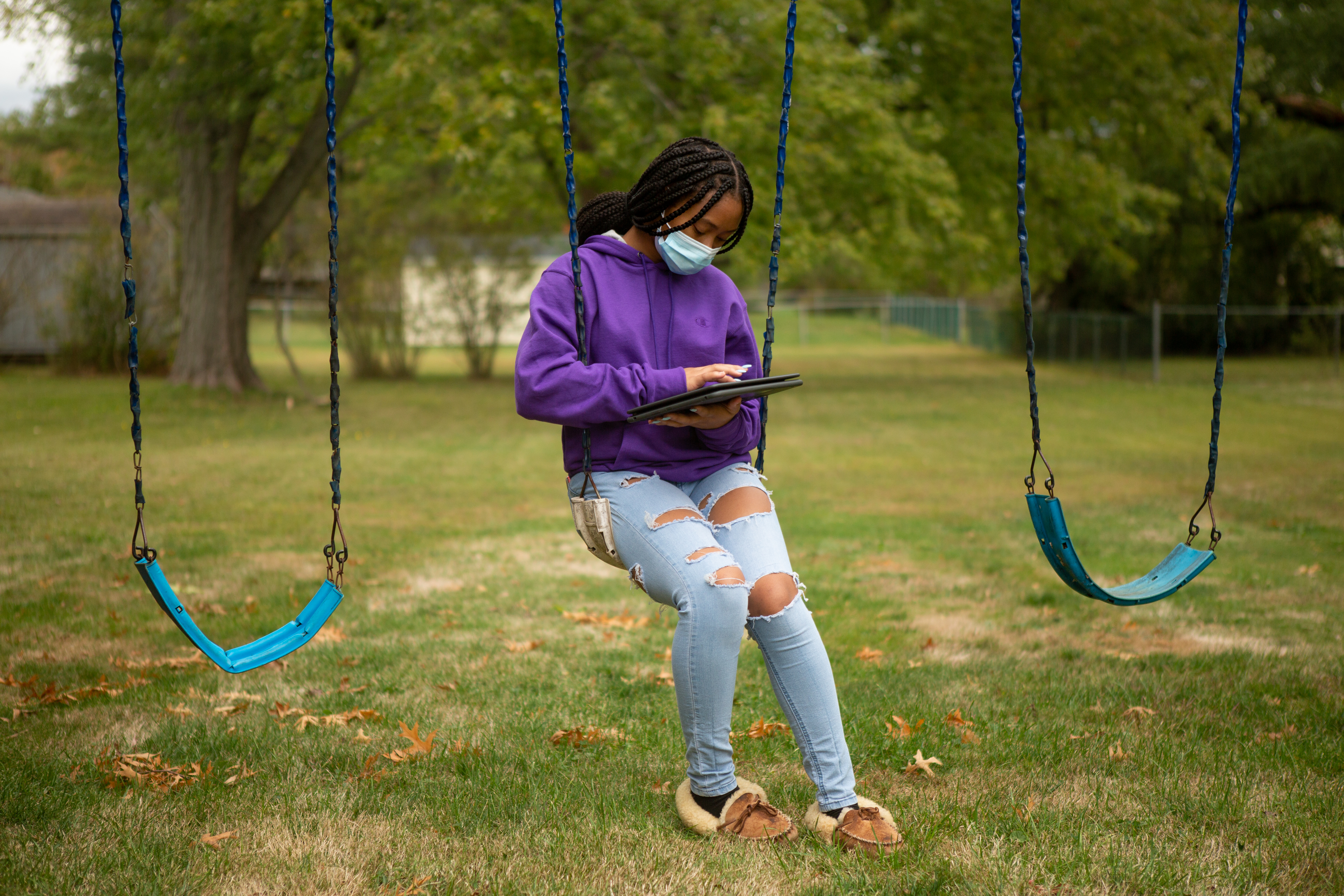 Middletown High School students Pilar Brooks sitting outside on a swing wearing a mask.