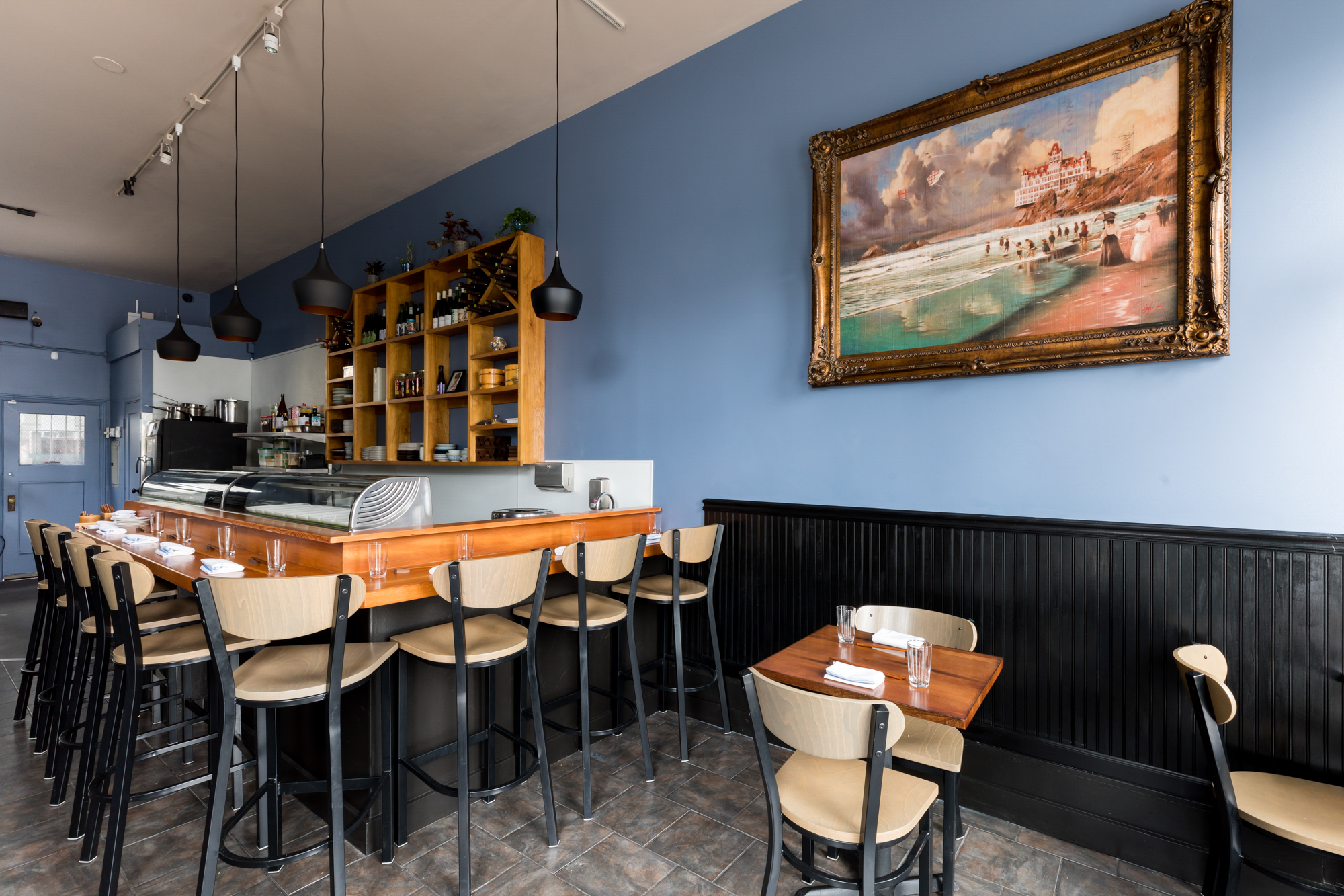 Inside Chisai Sushi Club, a small restaurant on Mission Street with blue walls and a warm wooden sushi bar with seats for 8 diners. A customer painting of Ocean Beach hang on one wall.