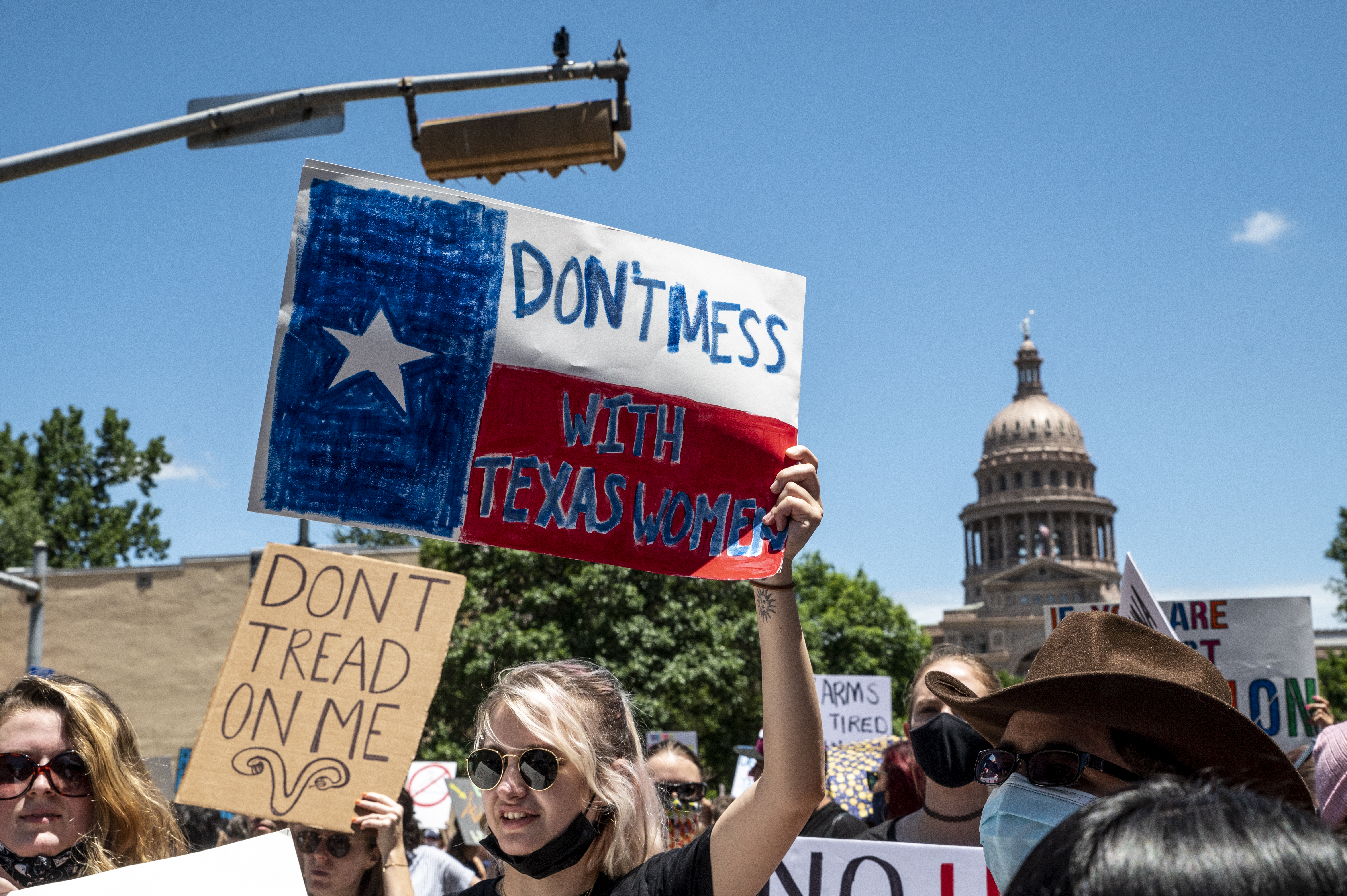 """A young woman holding a """"don't mess with Texas women"""" sign at a protest."""