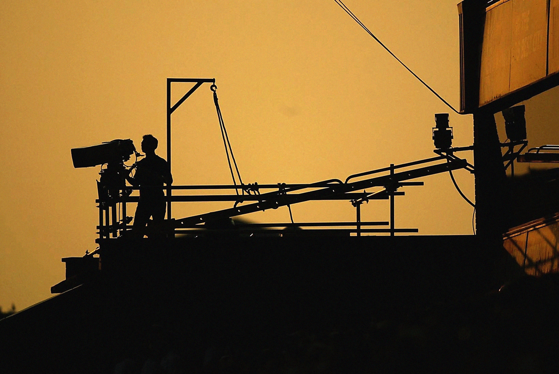 Television cameraman looks on as the sun sets in the background