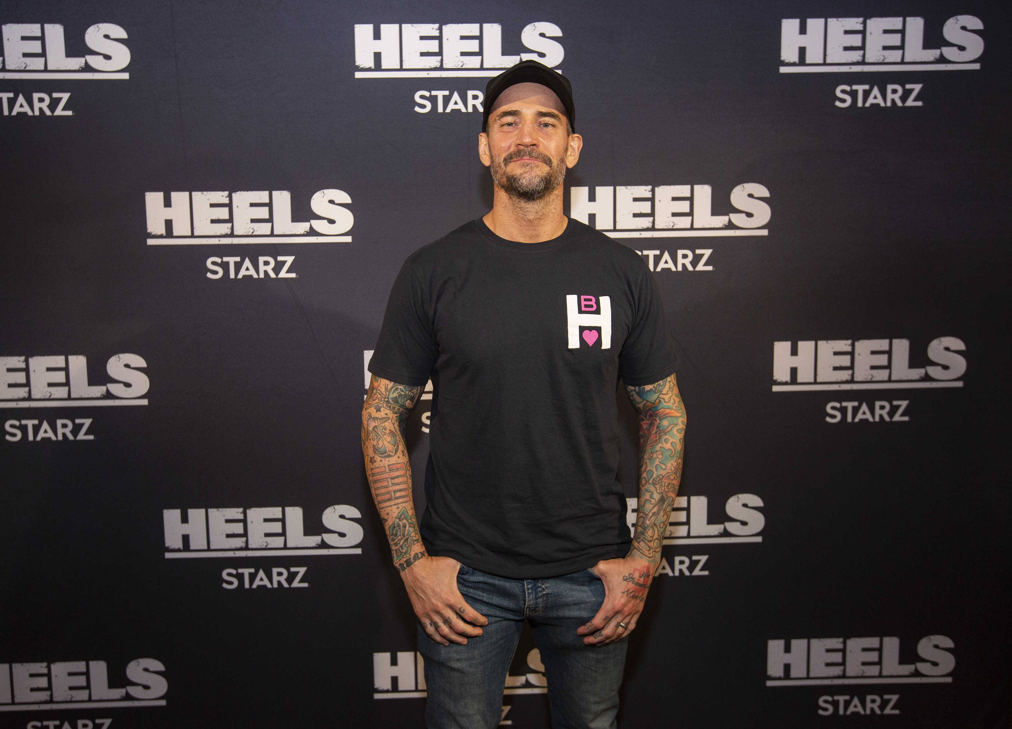 """Actor and wrestler Phil Brooks """"CM Punk"""" pose for a photo during a screening episode of the Starz channel's wrestling drama """"Heels"""" at the AMC River East Theater, on August 26, 2021 in Chicago, Illinois."""