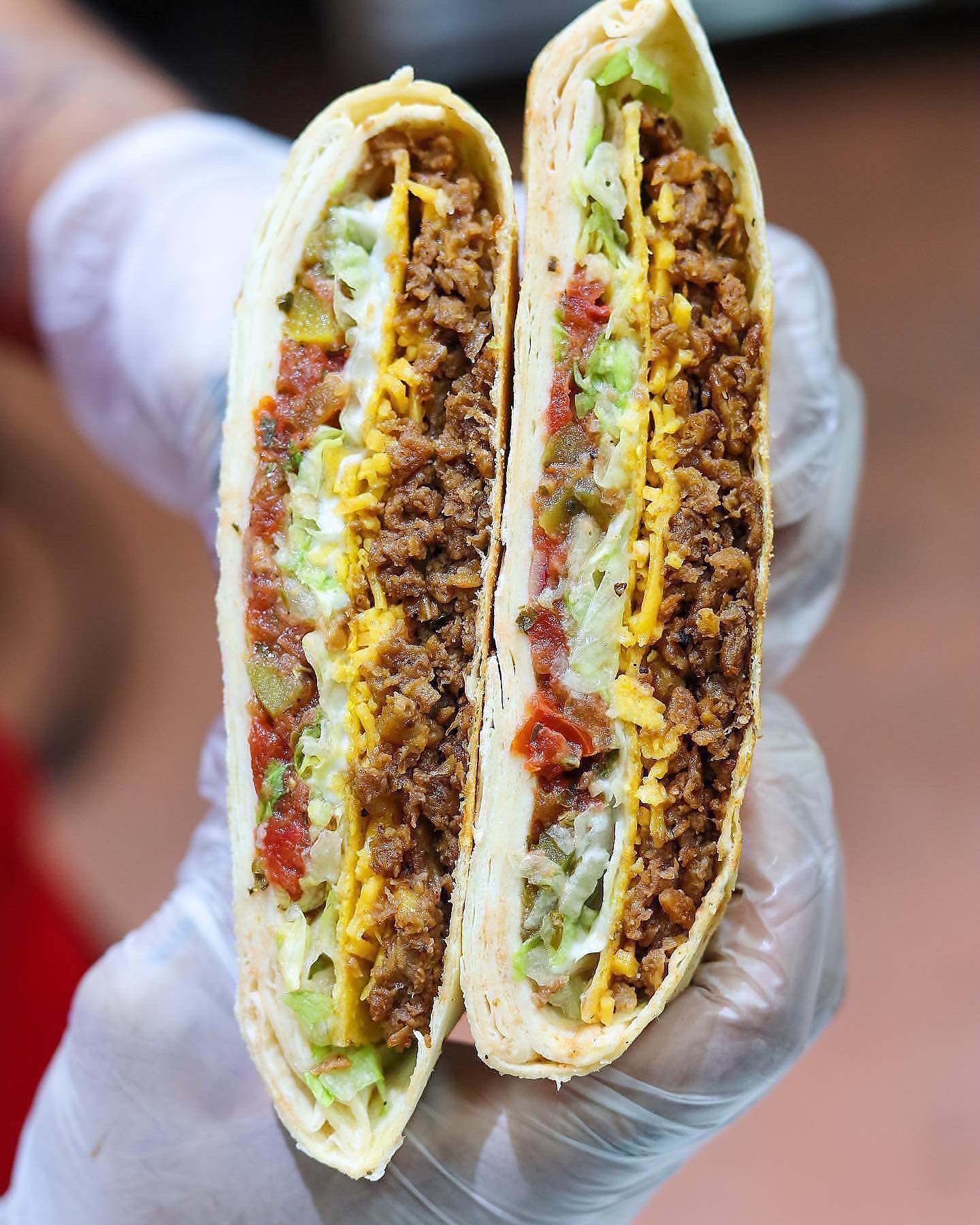 A vegan Crunchwrap, stuffed with plant-based meat, vegan cheese, lettuce, and pico de gallo, is sliced in half and held vertically by a gloved hand