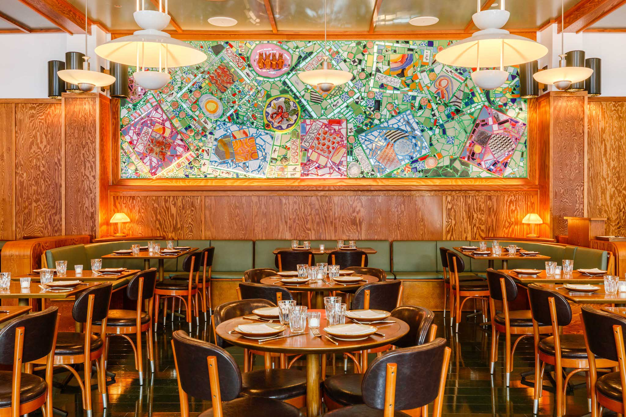 A dining room filled with wooden tables and chairs and a view of a colorful painting.