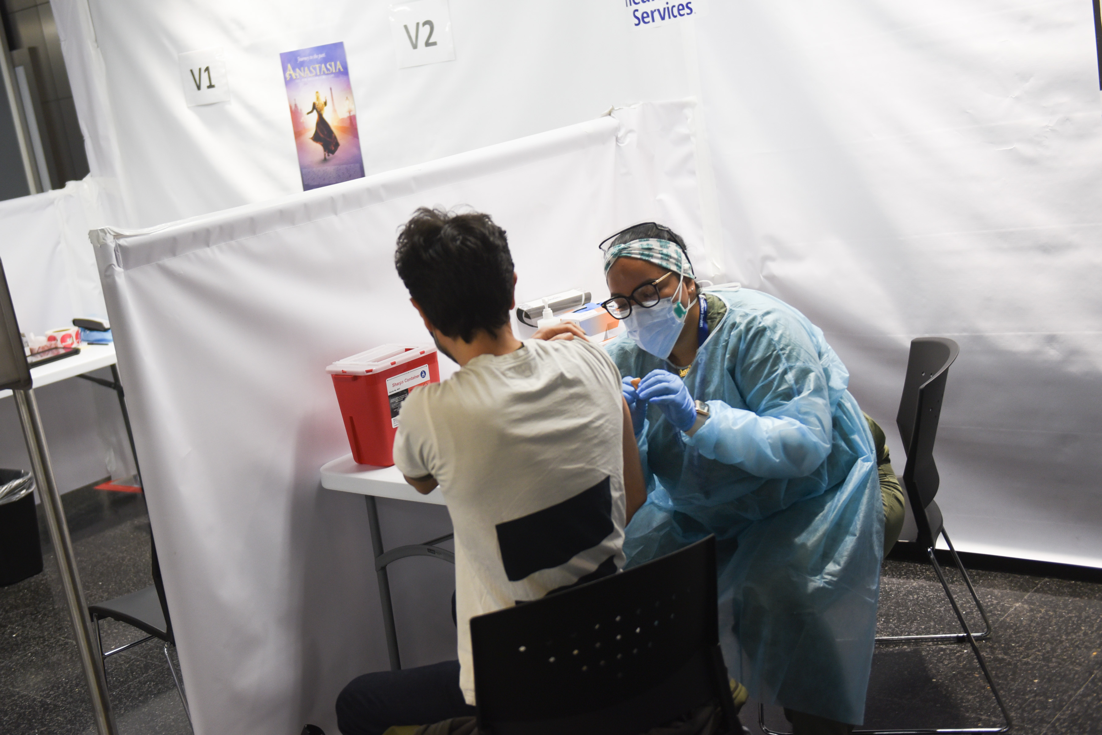 A health care professional in full protective clothing gives a dose of a COVID vaccine to a patient.