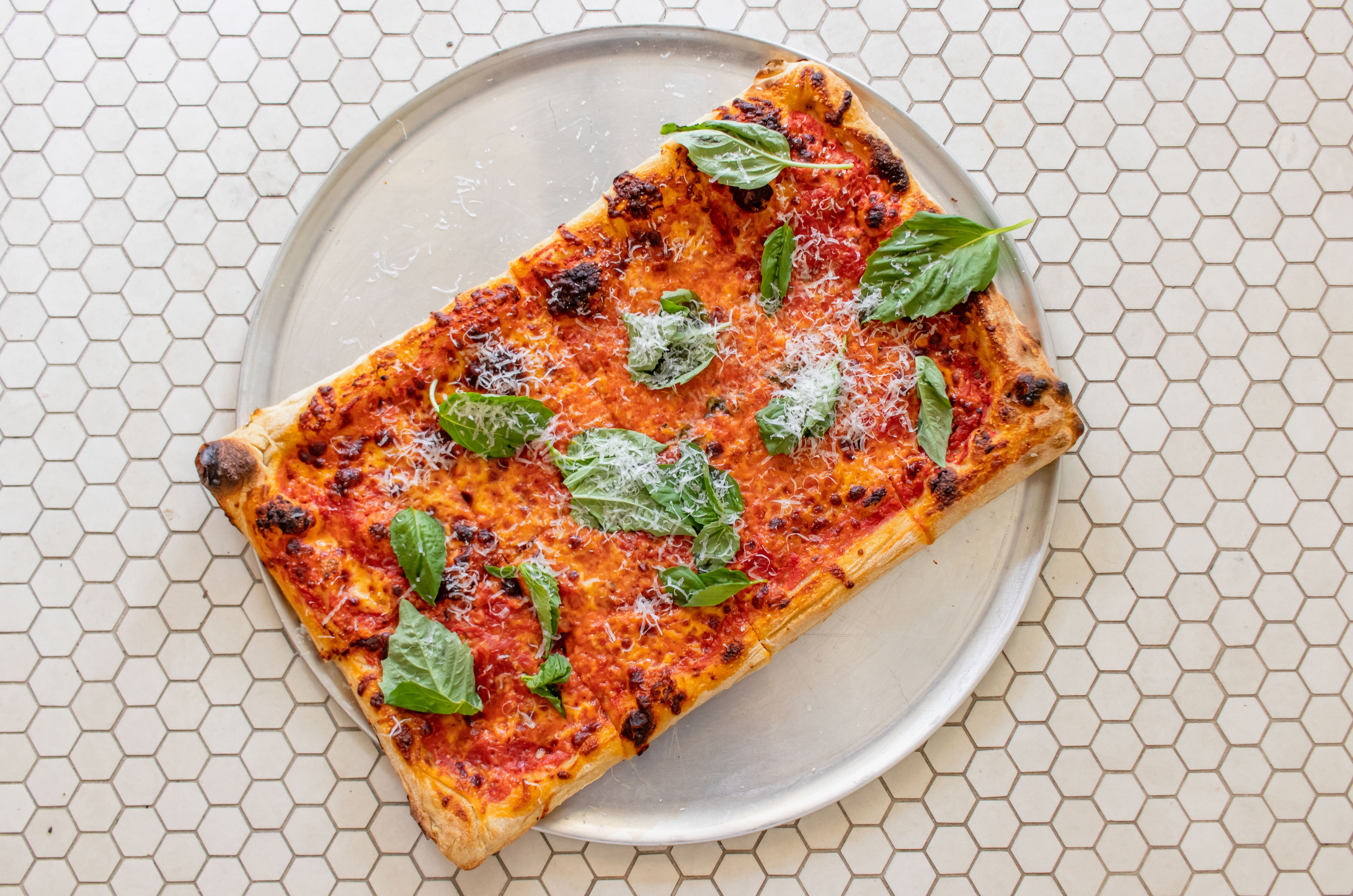 An overhead photograph of a square margherita pizza on a stainless steel tray.