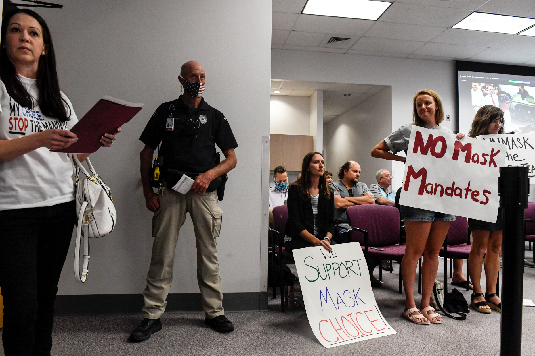 """A security officer in a brown and biege uniform stands against a wall surrounded by women carrying signs that say """"No mask mandates"""" and """"Support mask choice."""""""
