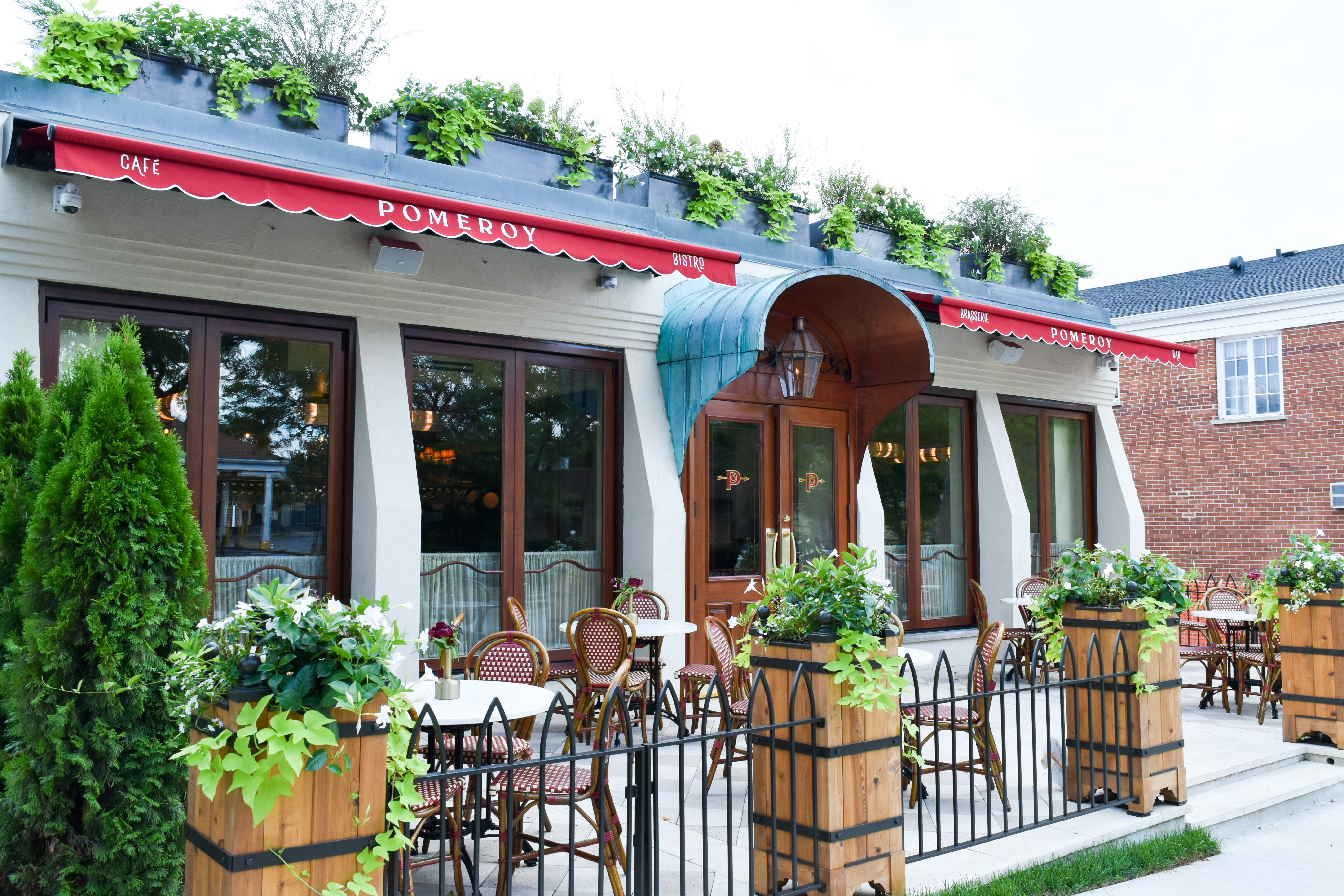 the exterior of a French restaurant with patio and awning