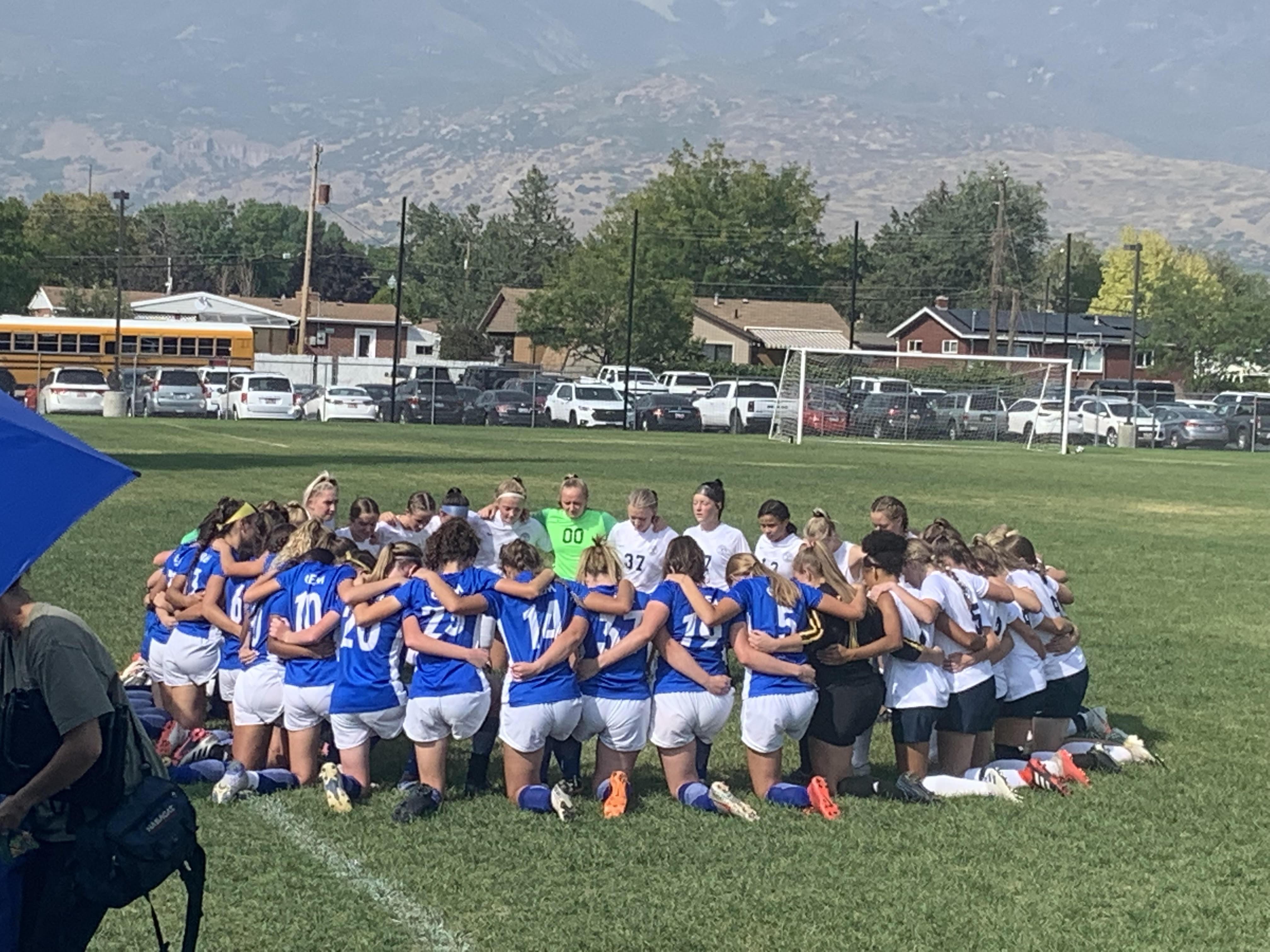 The Timpanogos High School varsity girls soccer team kneels in prayer with the opposing Orem High School team.