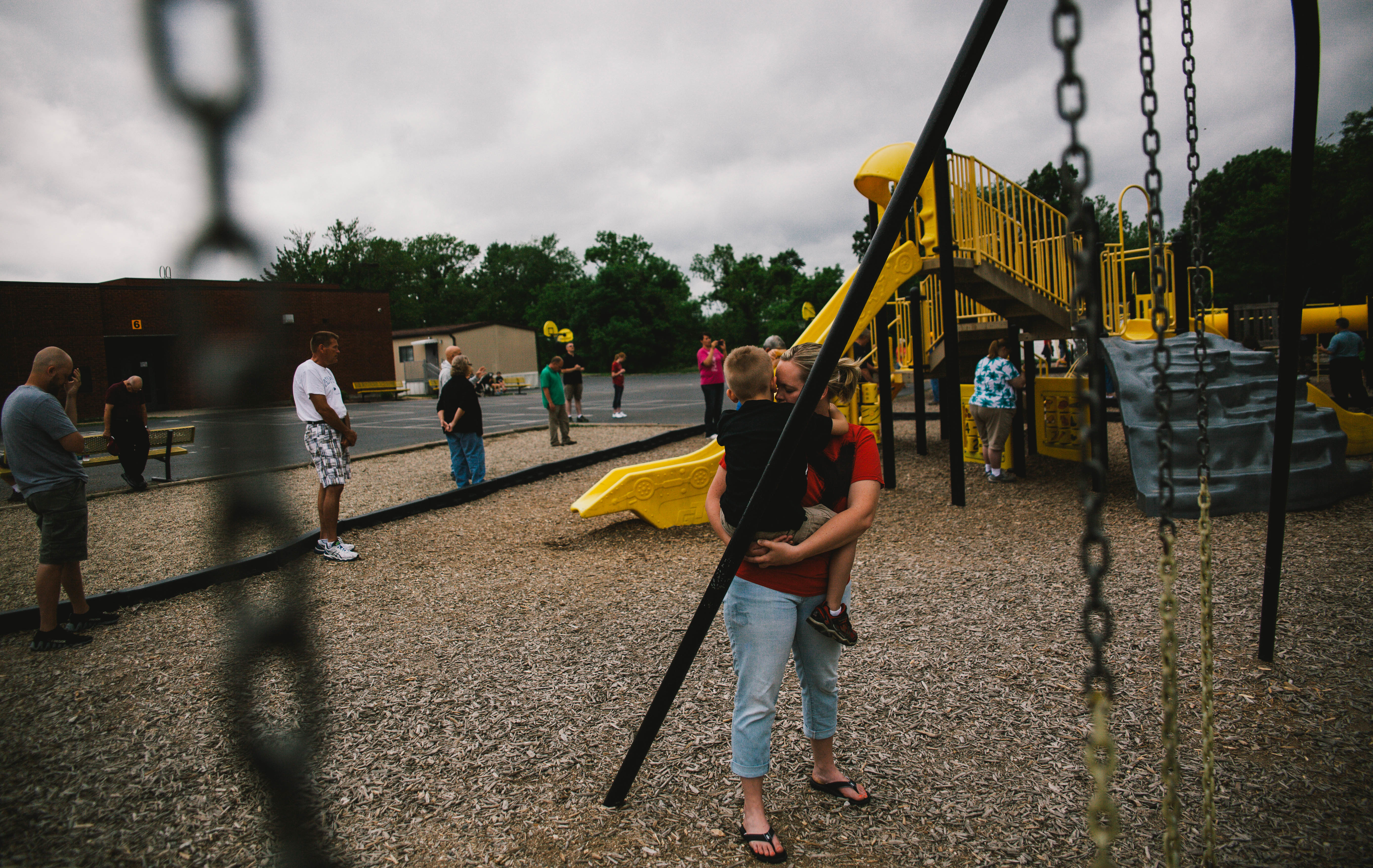 A woman holds her child next to a set of swings, as a circle of people pray around the edge of the playground.