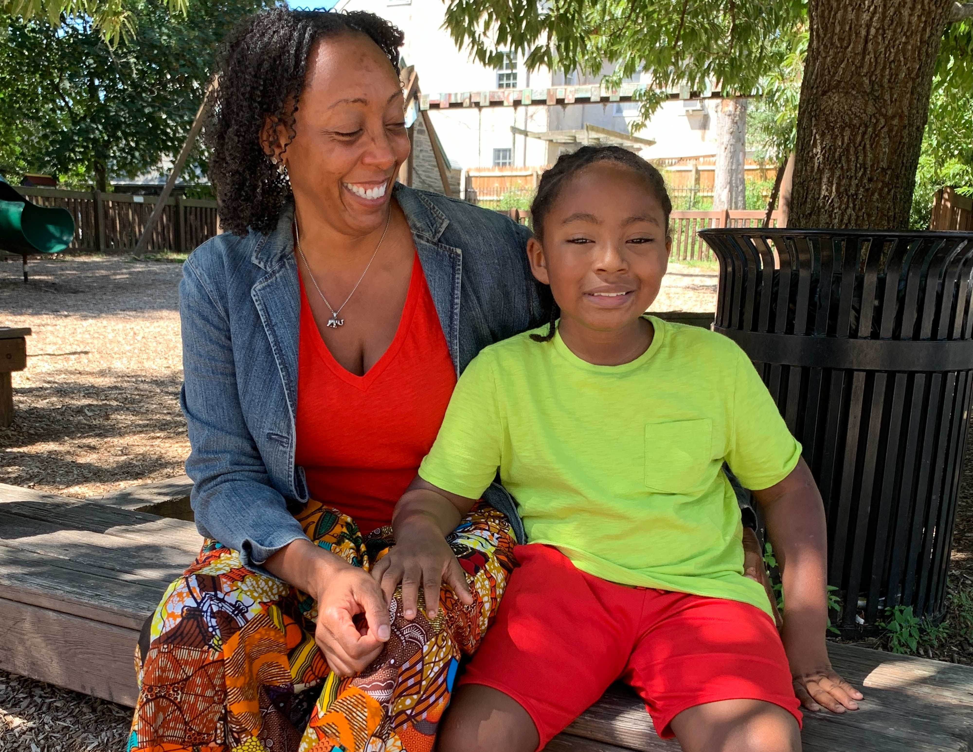 Jeannine Payne sits on a bench with her son Andre. She wears a red top and a denim jacket. He's wearing a neon green shirt and red shorts.