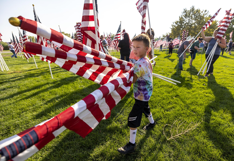 Ren Jensen carries American flags as he helps set up the Healing Field, a display of thousands of American Flags in Sandy, Utah.