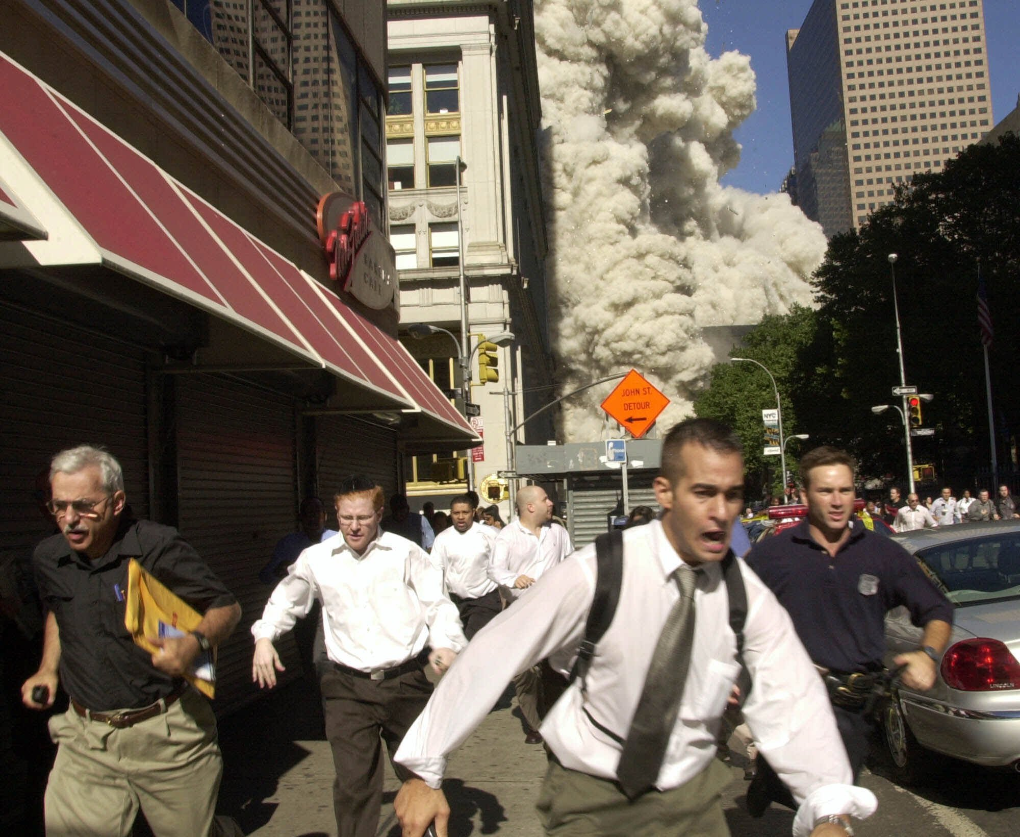 In this Tuesday, Sept. 11, 2001 file photo, people run from a cloud of debris from the collapse of a World Trade Center tower in New York.