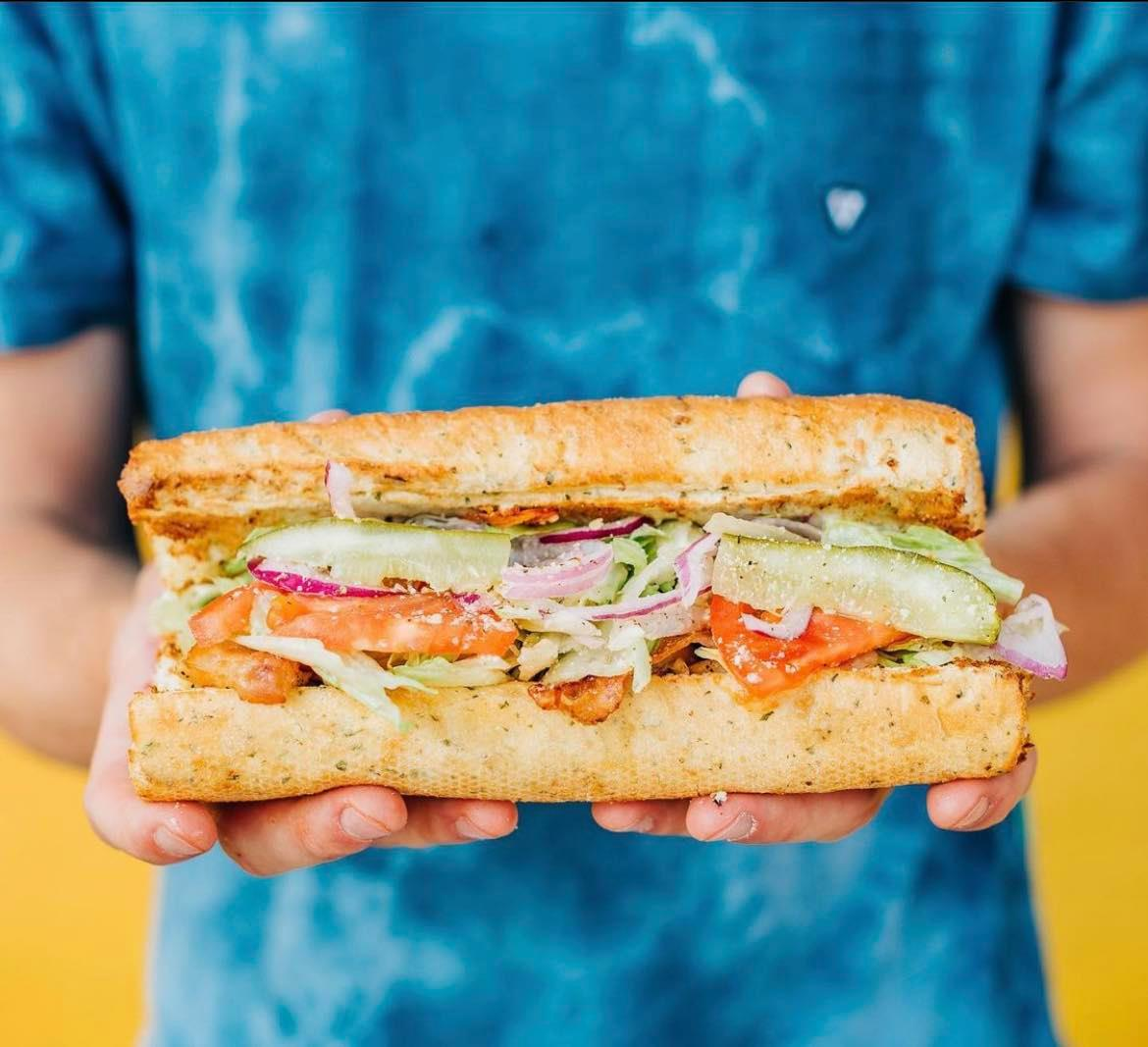 Against a yellow background, a person wearing a blue shirt holds a sub sandwich stuffed with veggies