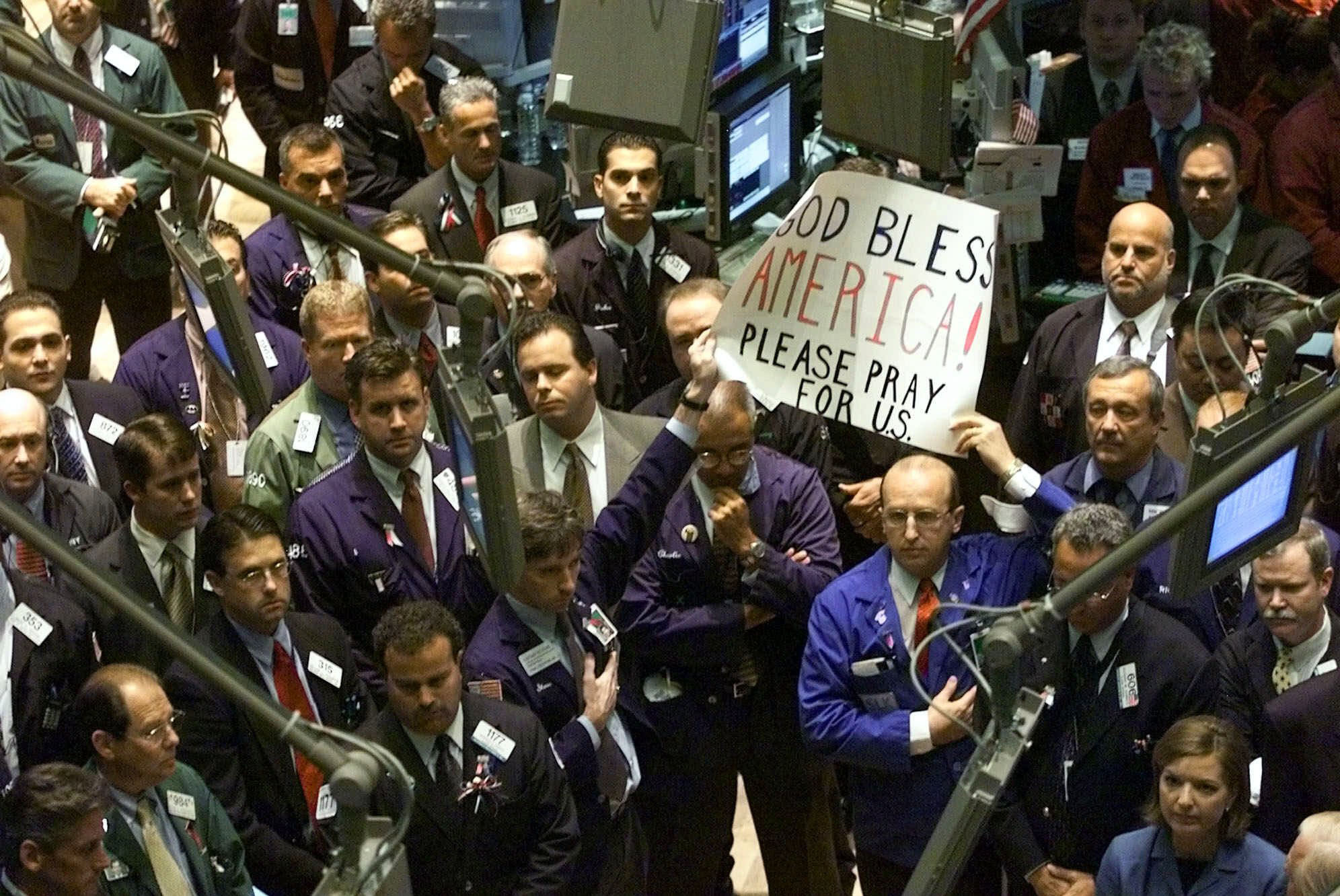 """Stock traders in New York hold a sign saying, """"God Bless America"""" after the attacks of 9/11."""