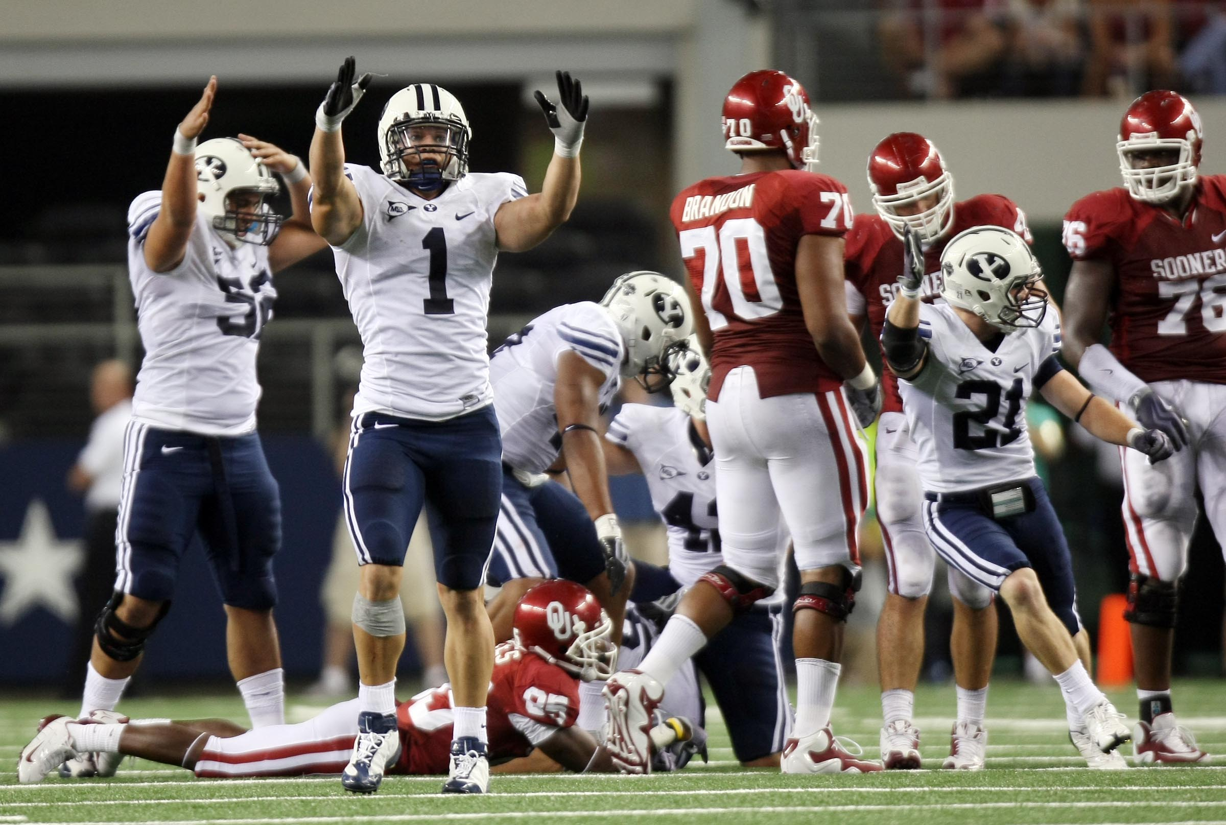 BYU's Jordan Pendleton (1) and other players celebrate a fumble recovery as BYU and Oklahoma play in Texas in 2009.
