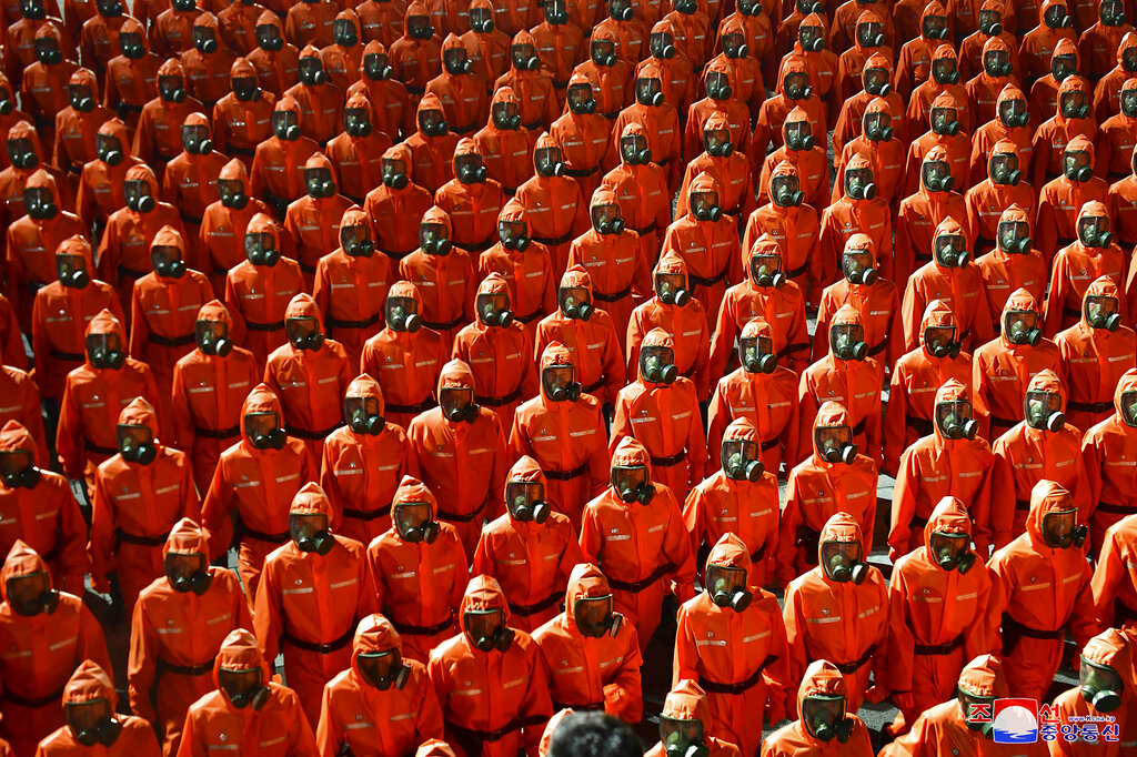 North Korean troops wearing gas masks and bright red suits.