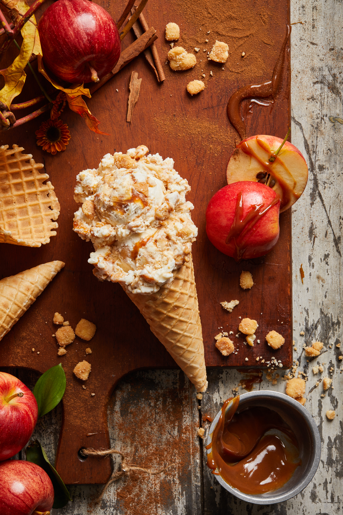 A scoop of ice cream on a waffle cone with apples, cones, and caramel surrounding it.