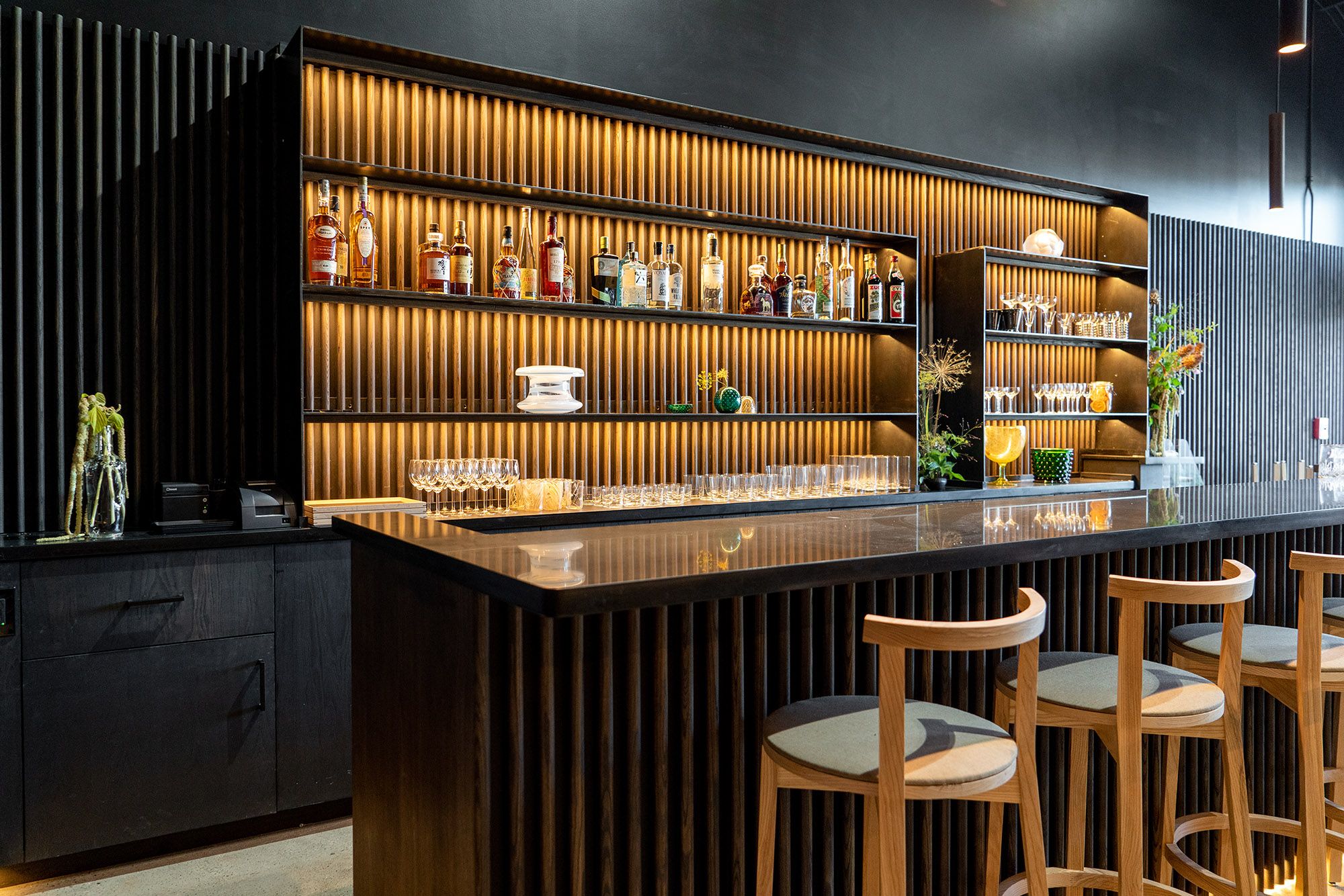 The bar at Tomo, lined with bottles and glasses, with orange accent lighting and dark paint on the walls.