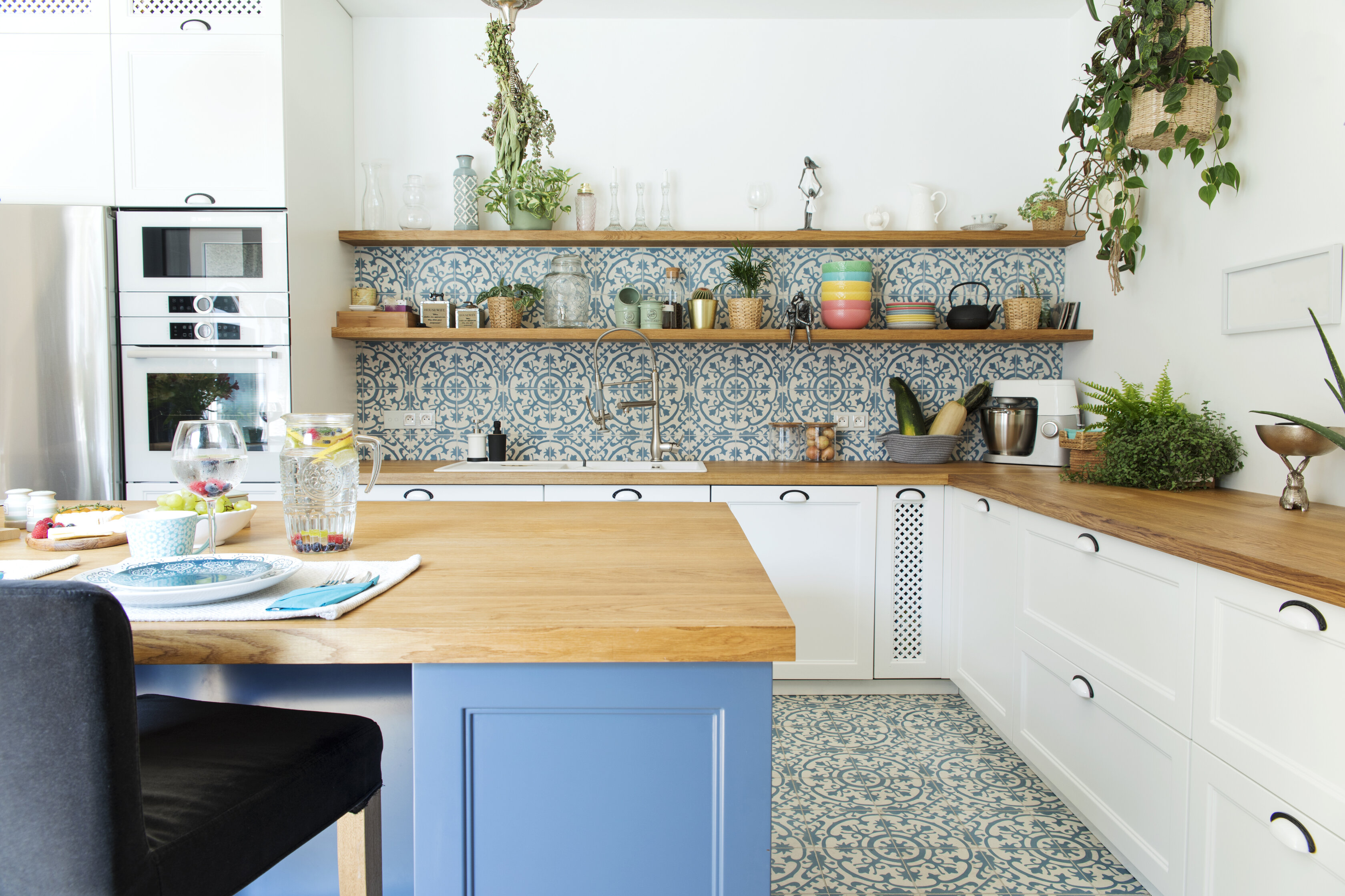 Kitchen with wood countertop, blue detailing, blue backsplash, and several houseplants.