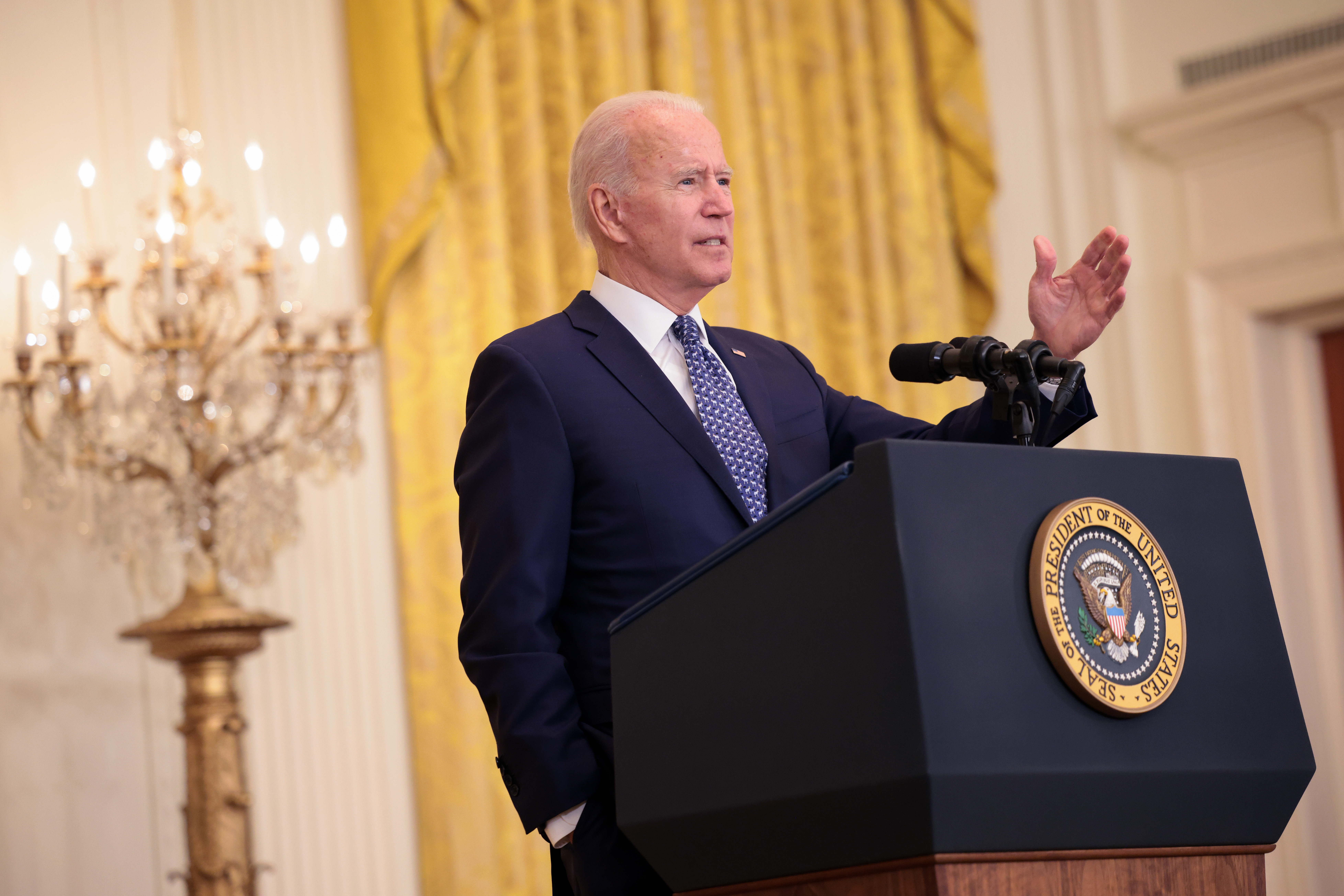 President Biden speaks at a podium marked with the presidential seal, with an ornate candelabra behind him.